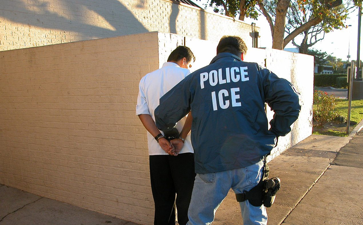 An Immigration and Customs Enforcement officer handcuffs an adult male.