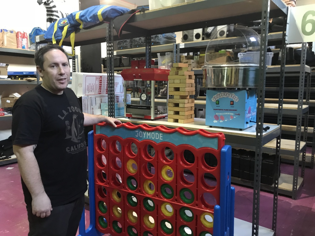 """Joe Fernandez stands next to a giant Connect Four set in his company's downtown Los Angeles warehouse. The Joymode co-founder says, among his customers, """"Pretty much anything you can get giant versions of is really popular."""" Feb. 5, 2018."""