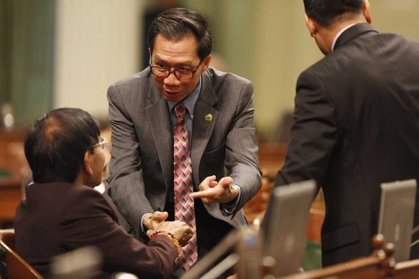 Ed Chau shakes the hand of another man in the Assembly chamber.