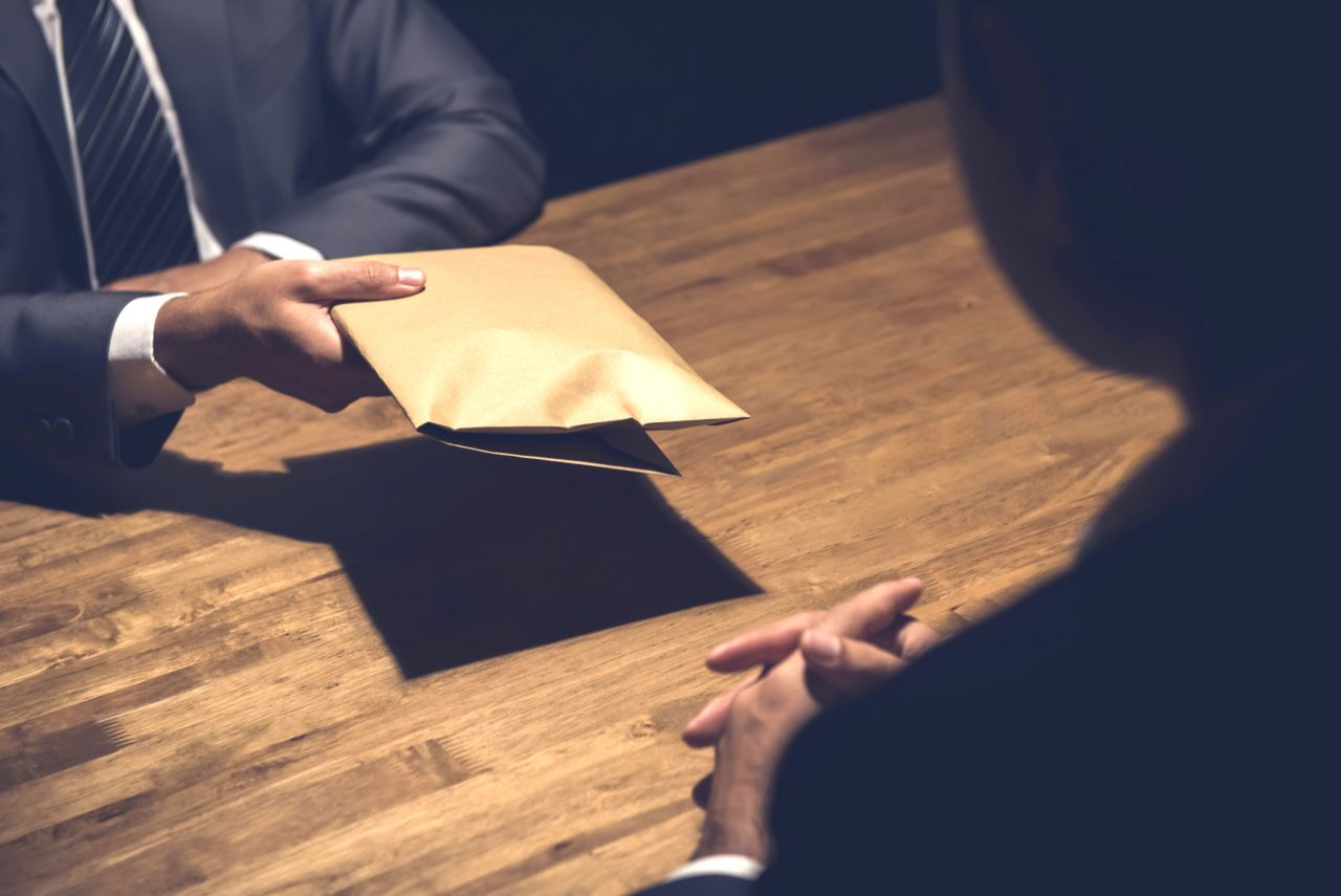 A man passing money to another in a brown envelope.