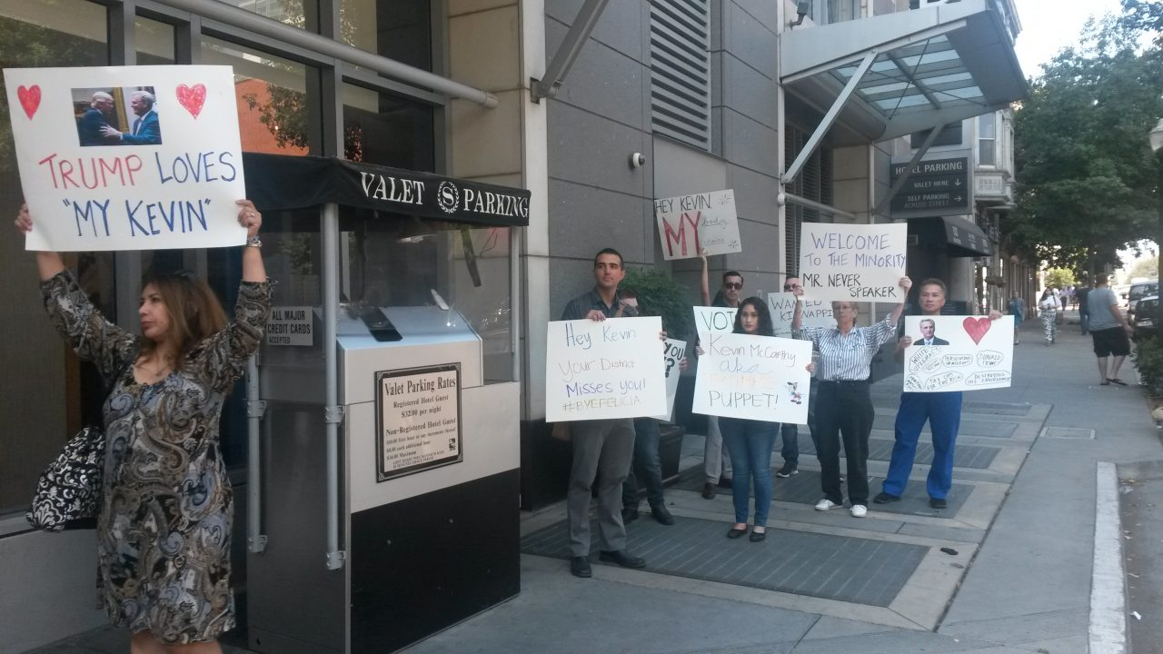 """Protesters carry signs that read """"Trump Loves 'My Kevin'"""" and """"Kevin McCarthy AKA Trump Puppet!"""" outside the Sheraton Grand Hotel in downtown Sacramento"""