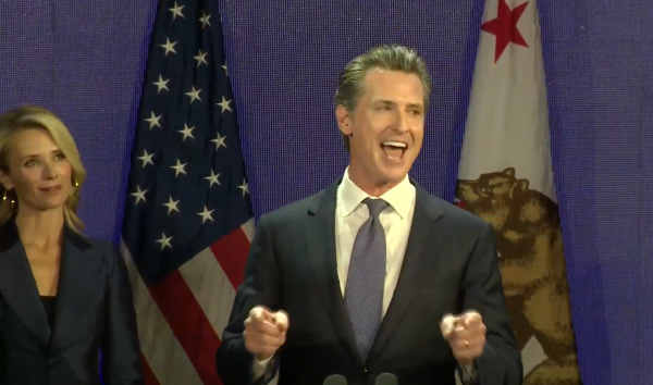 A victorious Gavin Newsom greets campaign supporters in Los Angeles on election night as his wife, Jennifer Siebel Newsom, looks on.