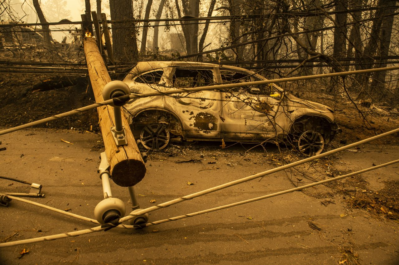 Charred car and downed power pole during the wildfire that destroyed the town of Paradise. Photo by Hector Amezcua/Sacramento Bee