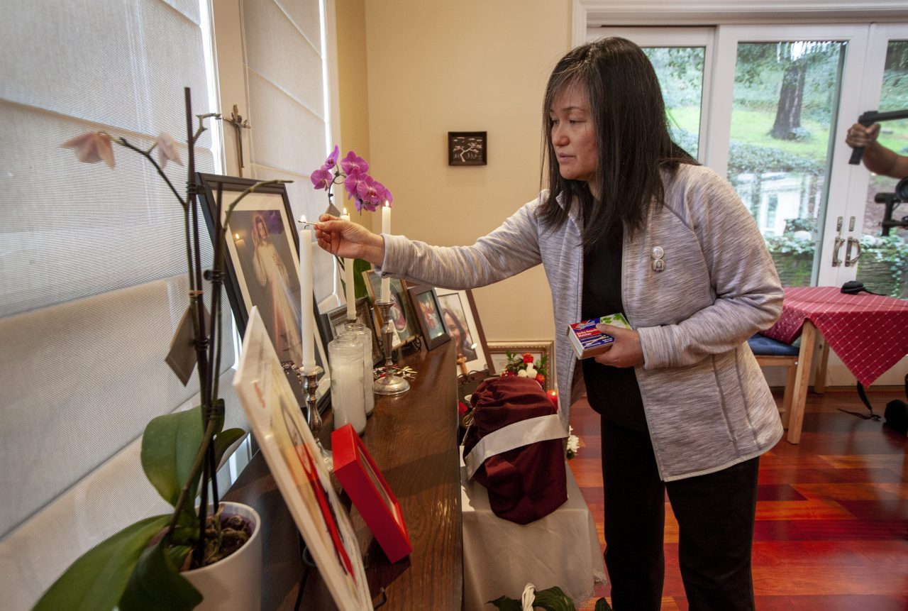 Seong Brown tends to the altar the family maintains in Elizabeth's honor at their Santa Rosa home. Photo by Penni Gladstone for CALmatters