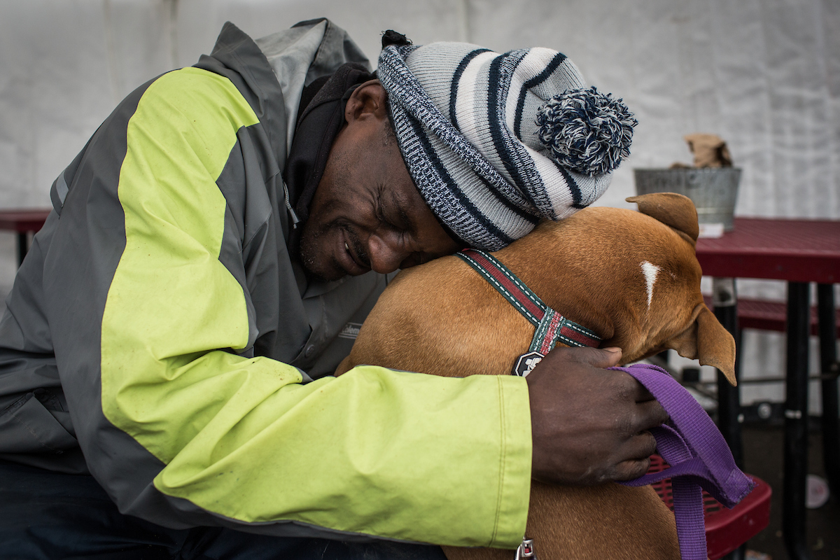 Lamont Grant hugs his dog, Bandit, at the Sacramento Winter Triage Center. Photo by Max Whittaker for CALmatters