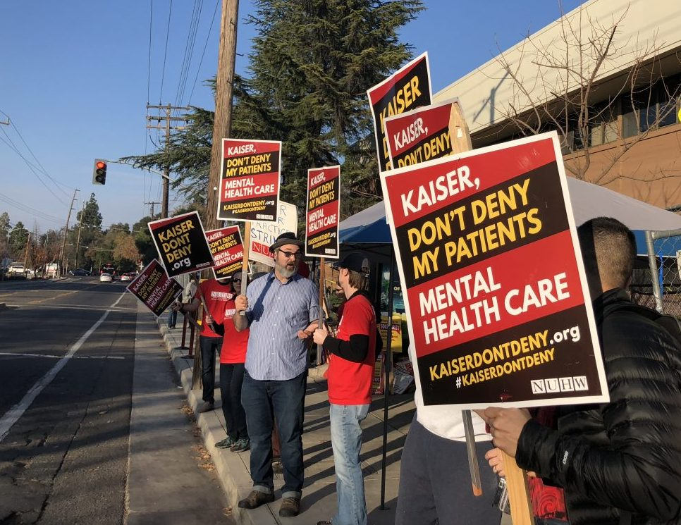 A group of Kaiser employees and their supporters protest outside Kaiser Permanente Sacramento Medical Center on December 11, 2018—part of a five-day action by some therapists, social workers and psychologists who called on Kaiser to boost mental health staffing. Photo by Byrhonda Lyons for CALmatters