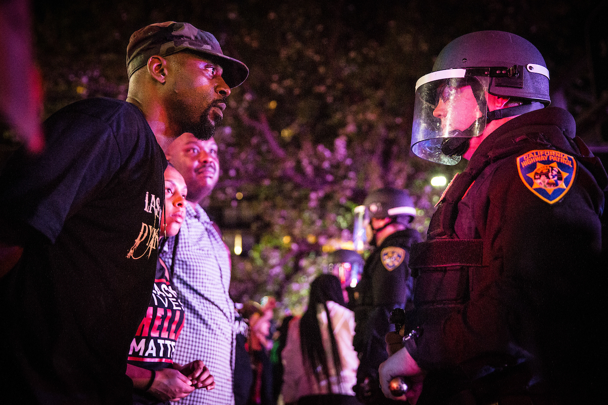 Photo of a Black Lives Matter protestor staring at a California Highway Patrol officer during a protest in Sacramento following the police shooting of Stephon Clark.