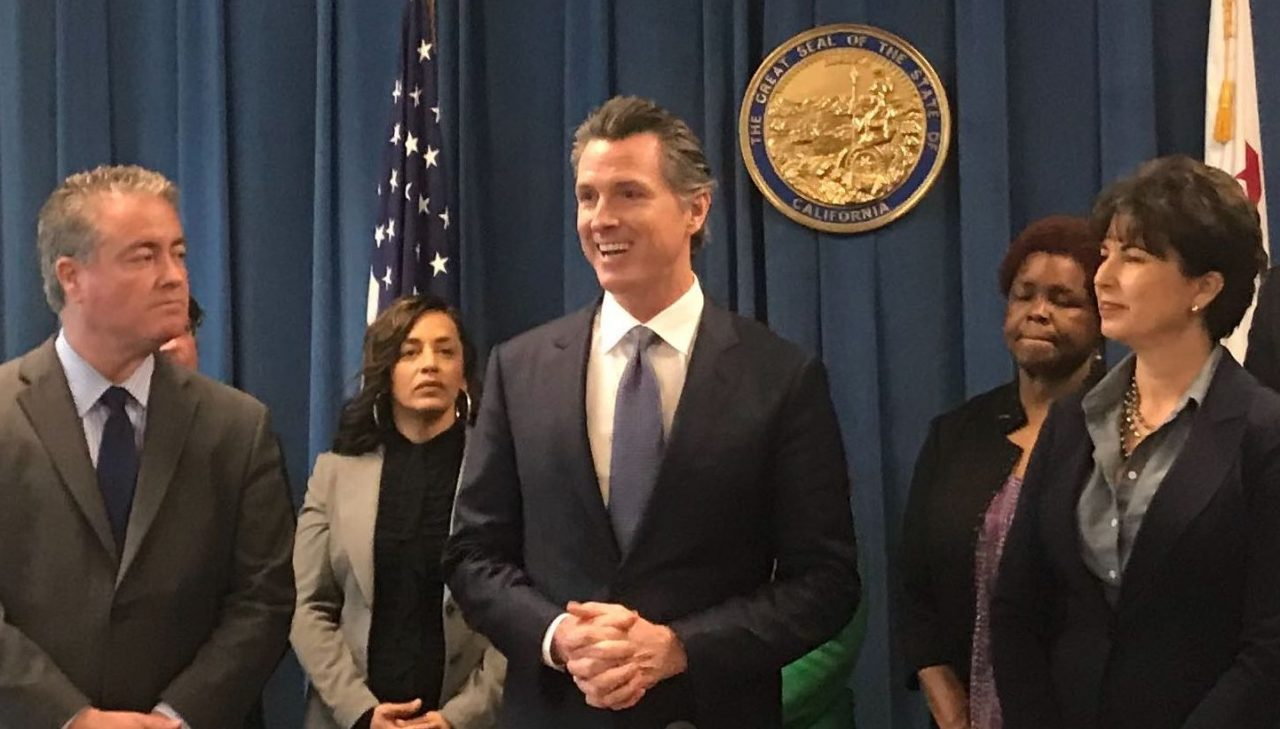 Gov. Gavin Newsom, flanked by authors Sen. Connie Leyva and Assemblyman Patrick O'Donnell, prepares to sign a charter school transparency bill. Photo for CALmatters by Ricardo Cano