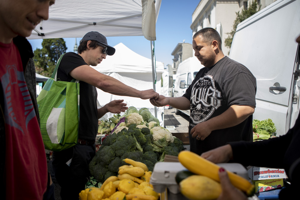 Berkeley resident Alex McNall uses CalFresh tokens to purchase vegetables at the Ecology Center farmers' market in downtown Berkeley on July 13, 2019. CalFresh participants can purchase tokens at the market using their benefits card and can receive up to $10 in additional tokens specifically for fruits and vegetables.
