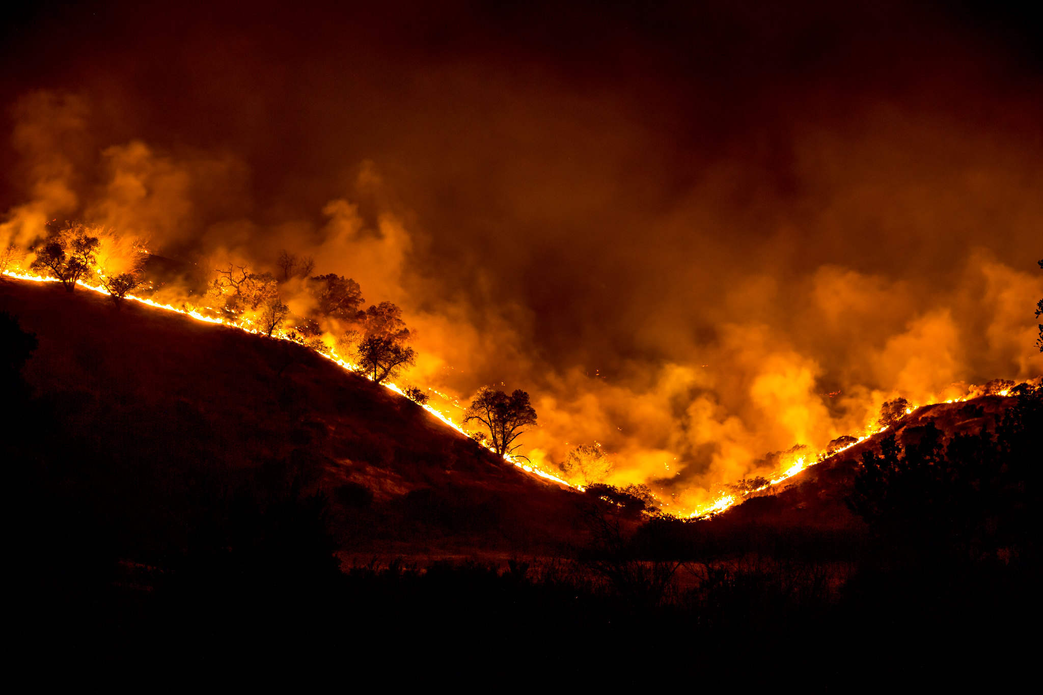 A fire crowning two hills, with black trees silhouetted against the orange glow.