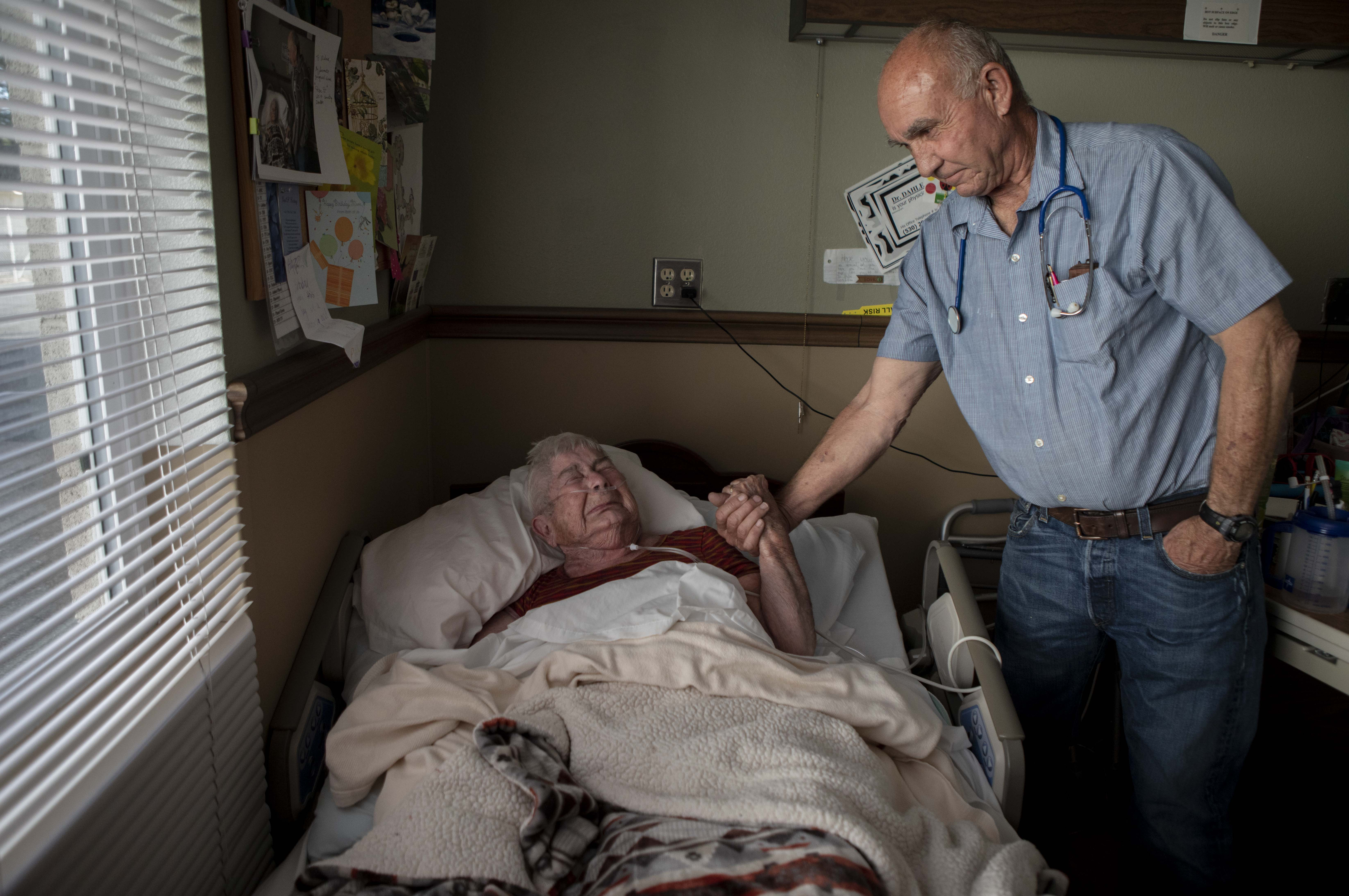 Wilma Chesbroe, a patient and long-time friend of Dr. Dan Dahle, sobs and holds hands with the doctor as they joke and reminisce about the many years they spent working together at the Fall River Mill hospital. Photo by Anne Wernikoff for CalMatters