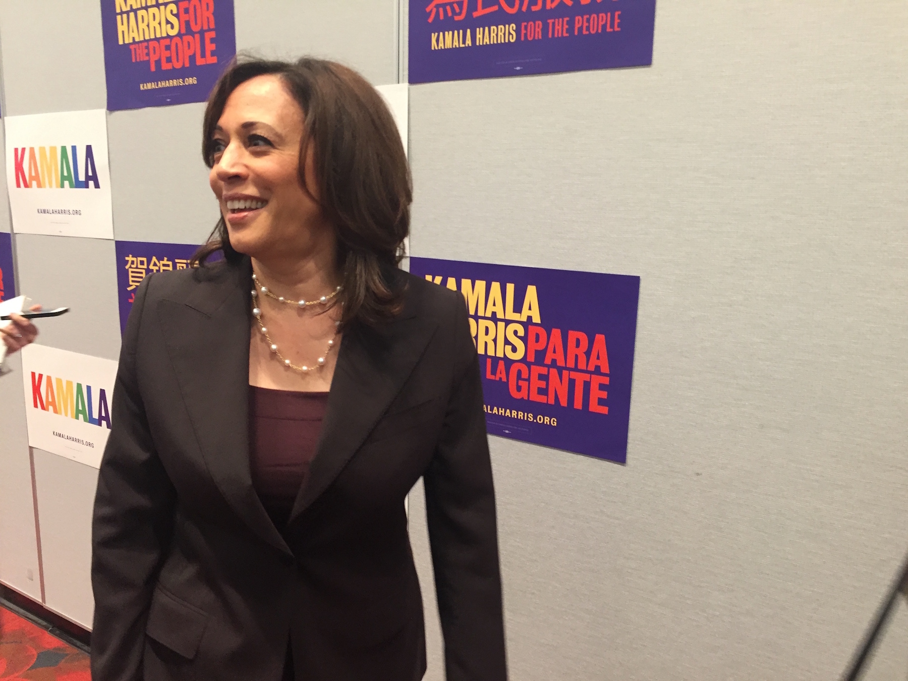 Harris speaks to reporters in front of a campaign backdrop in San Francisco