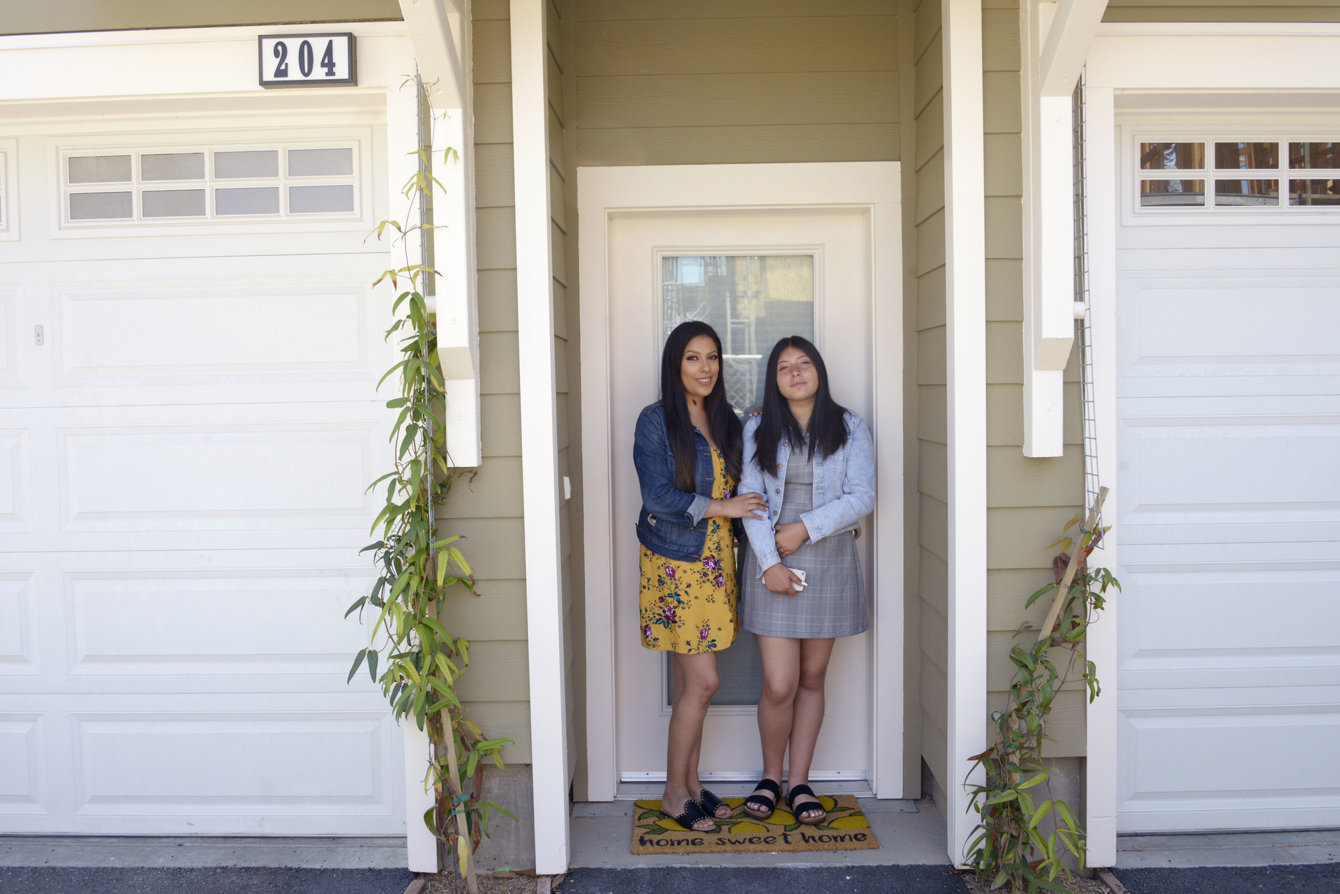 Julieta Aquino and her daughter Alexys in front of their new home in Fremont, which they moved into in June. Aquino helped build the housing complex as a participant in an East Bay-Silicon Valley Habitat for Humanity program.  Photo by Stephanie Lister/KQED
