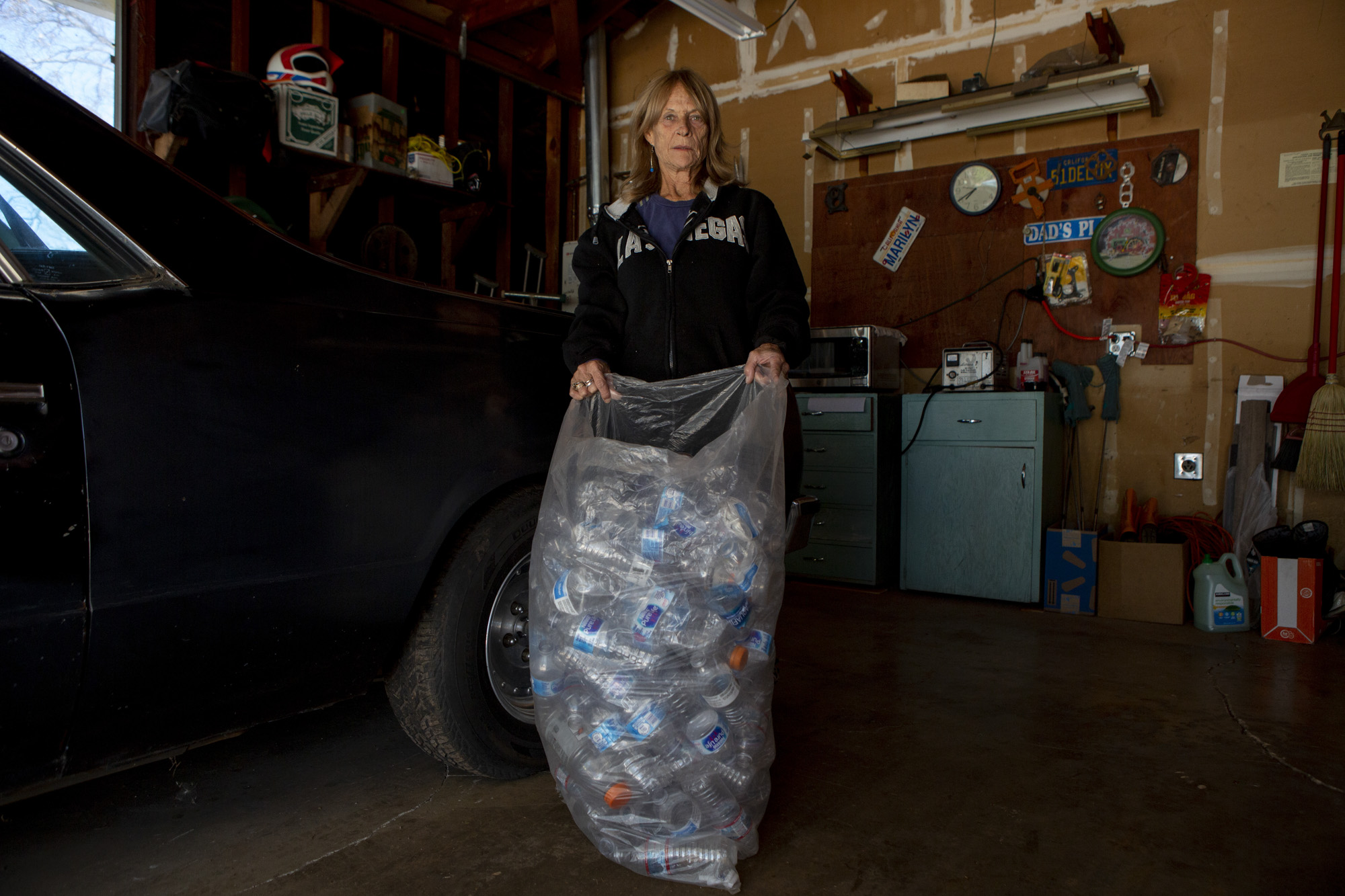 Paradise resident Marilyn Adams in her garage with a bag of plastic water bottles. Photo by Anne Wernikoff, CalMatters