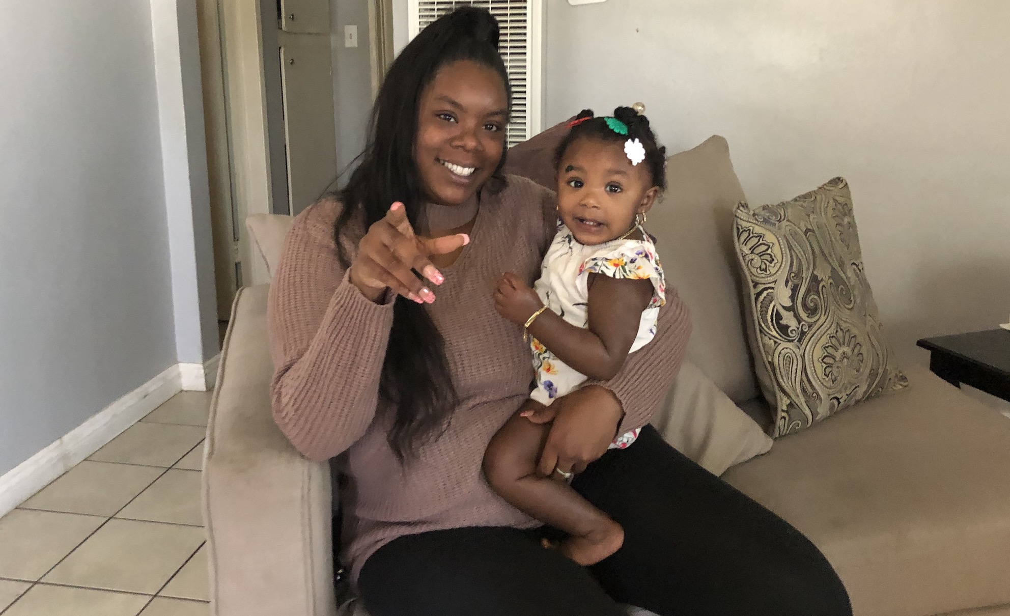 Ebony Palmer and her young daughter in her apartment. Photo by Matt Tinoco/KPCC