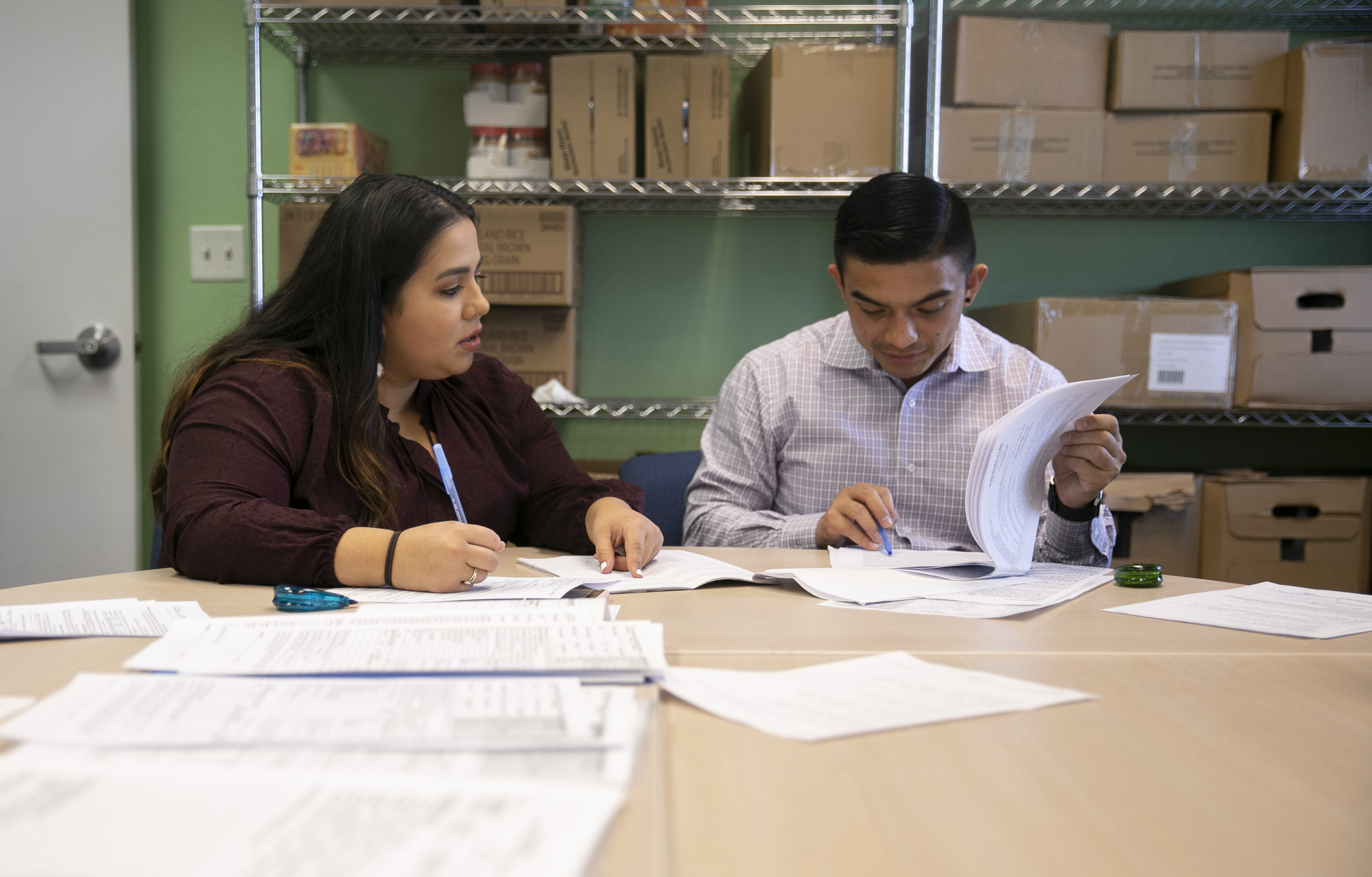 Volunteer Daniella Martinez, left, and Shane Sagisi, a law clerk with San Mateo County Legal Aid, fill out unlawful detainer forms during a housing clinic at the Colma Civic Center. Photo by Anne Wernikoff for CalMatters