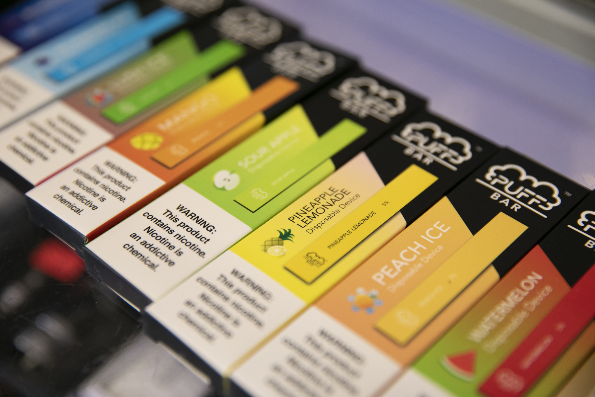 Disposable e-cigarettes with flavors like pineapple lemonade, sour apple and watermelon at a smoke shop