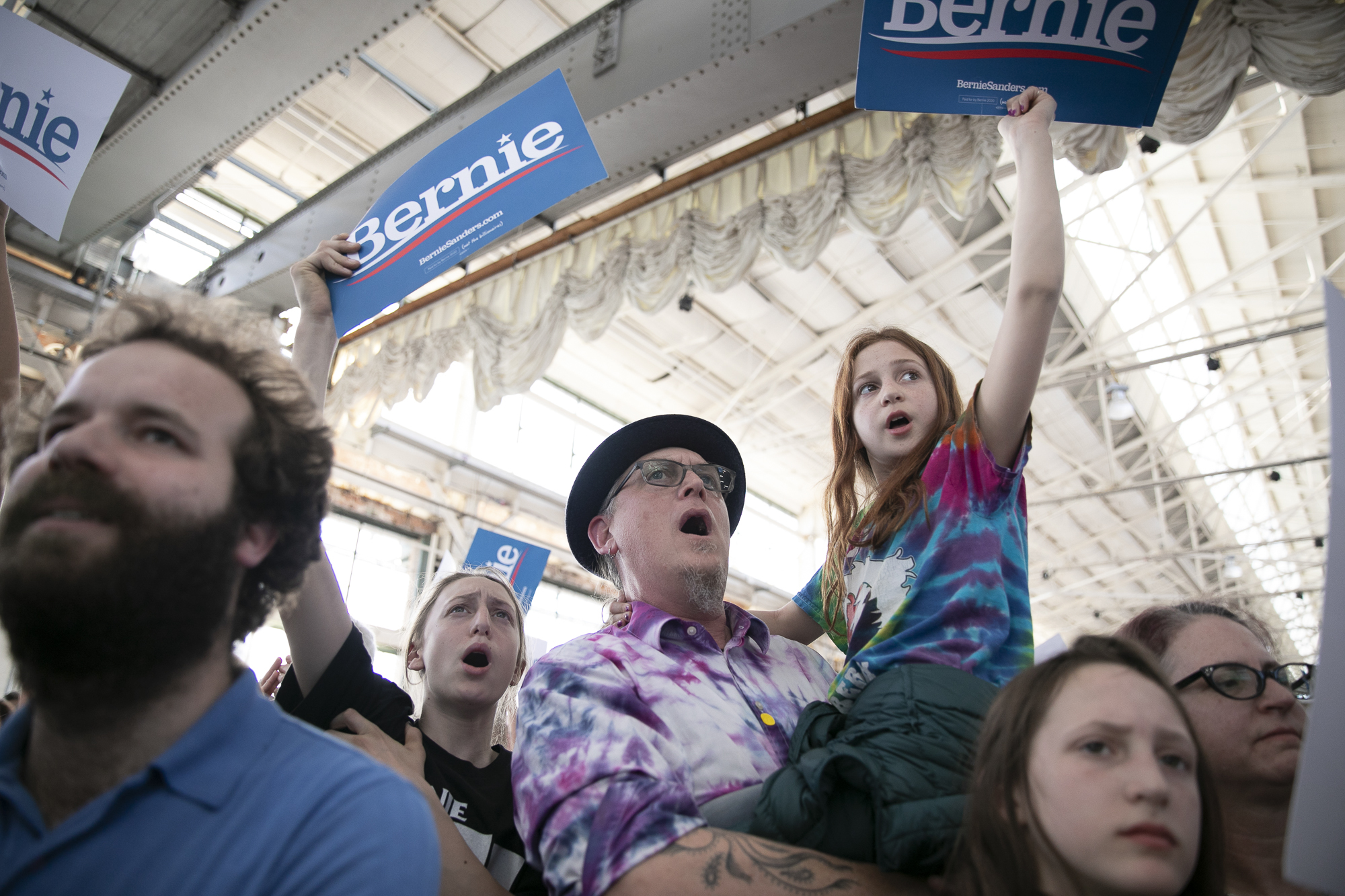 Sebastopol residents Joseph Mastrolia and his children Domino, 13, left and Talulah, 11 cheer during a Bernie Sanders campaign rally in Richmond, CA on February 17, 2020. Photo by Anne Wernikoff for CalMatters