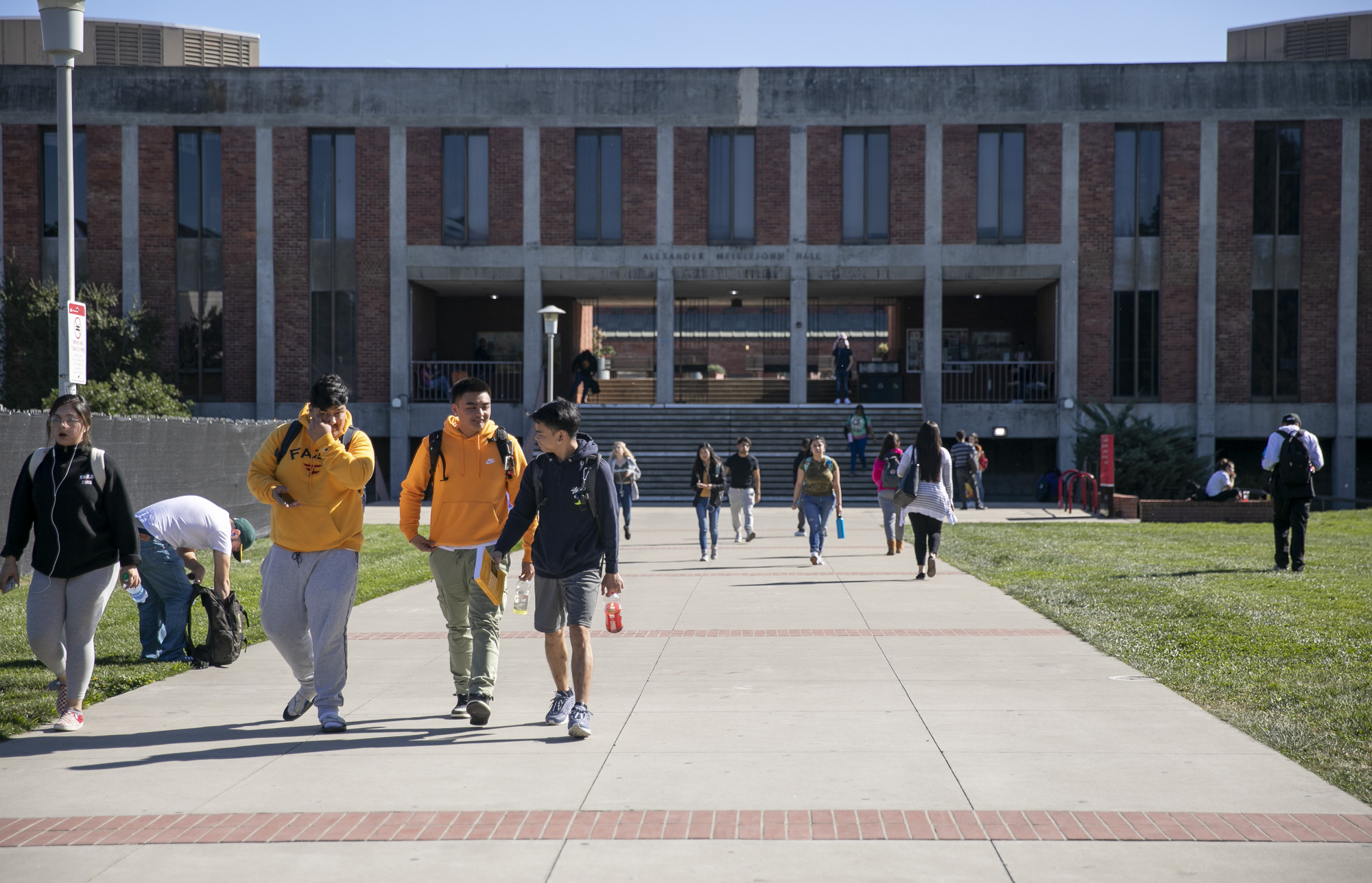 Students walk near Meiklejohn Hall at California State University East Bay. Photo by Anne Wernikoff for CalMatters