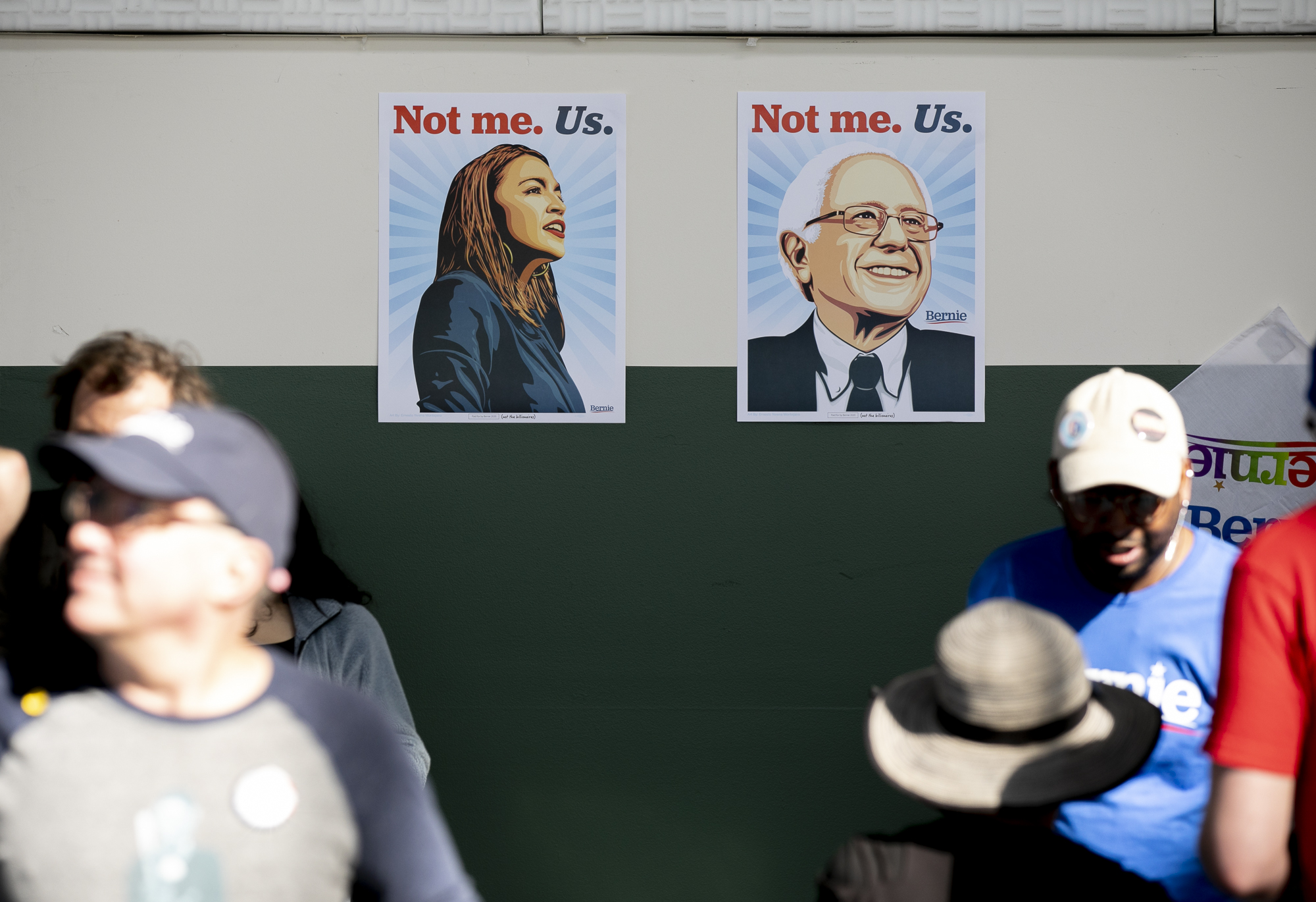 Posters of U.S. Representative Alexandria Ocasio-Cortez and democratic presidential candidate Bernie Sanders at a Sanders campaign rally in Richmond, CA, on February 17, 2020. Photo by Anne Wernikoff for CalMatters