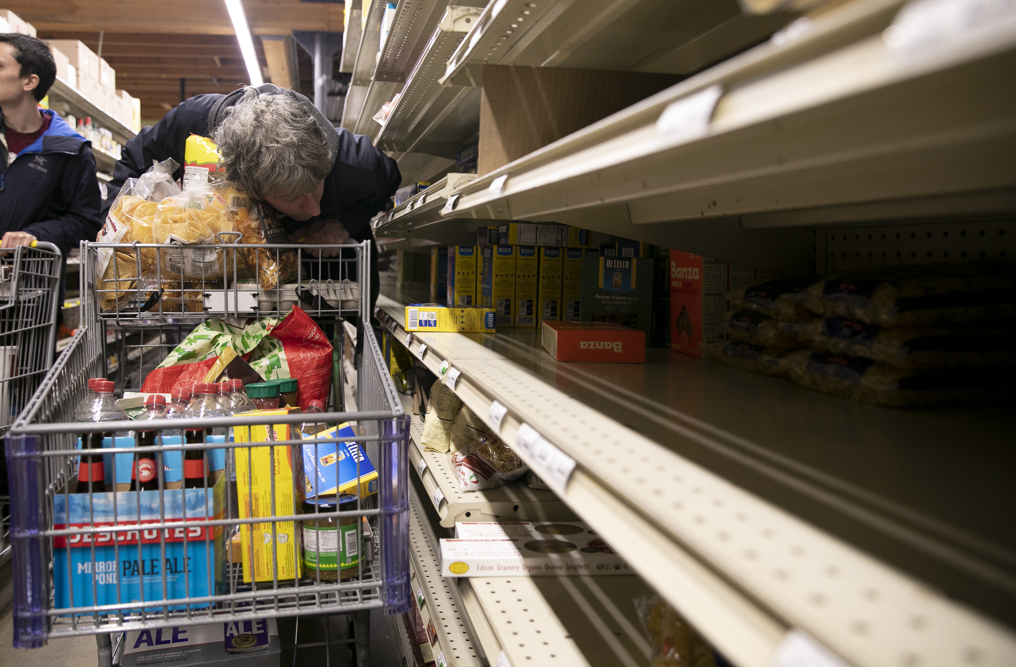 Andy Jordan peers into an empty shelf in the pasta aisle at Berkeley Bowl on March 13, 2020.