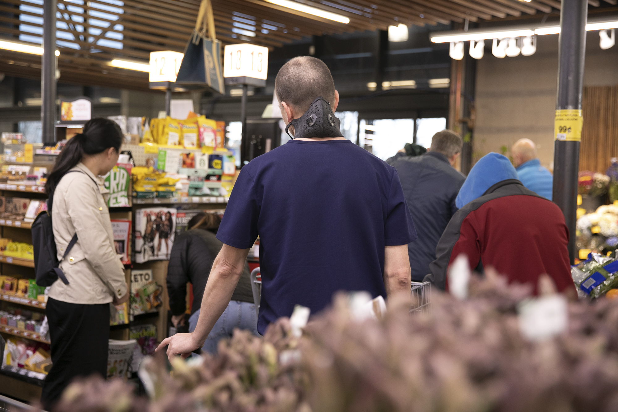 A man with a protective mask around his neck waits in the checkout line at Berkeley Bowl on March 13, 2020. Photo by Anne Wernikoff for CalMatters
