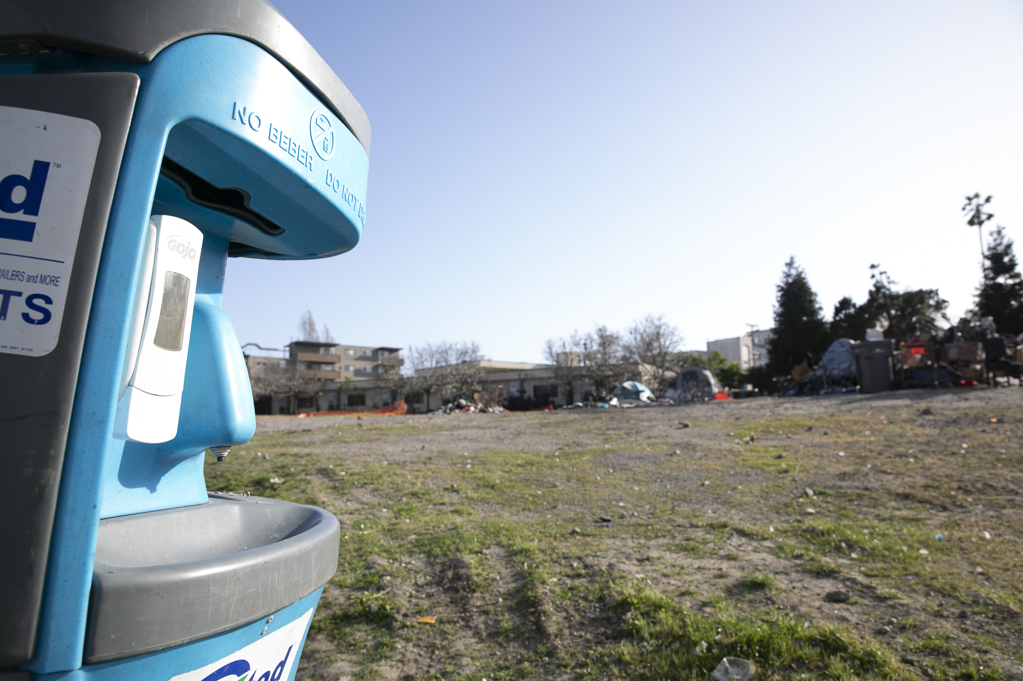 A hand-sanitizing station at a homeless encampment near Oakland city hall. Photo by Anne Wernikoff for CalMatters