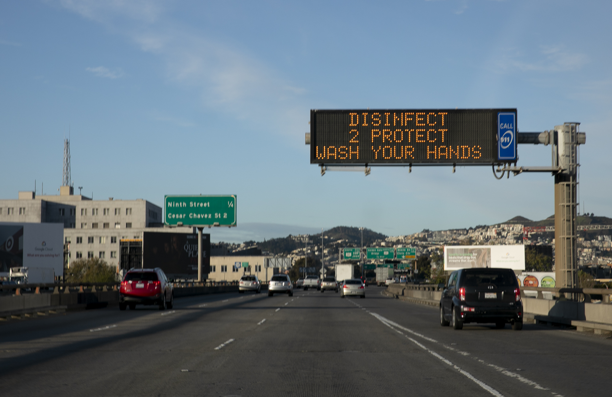 A sign reminding drivers to wash their hands hangs above I-280 in San Francisco on the first day of the three-week shelter in place mandate. Photo by Anne Wernikoff for CalMatters