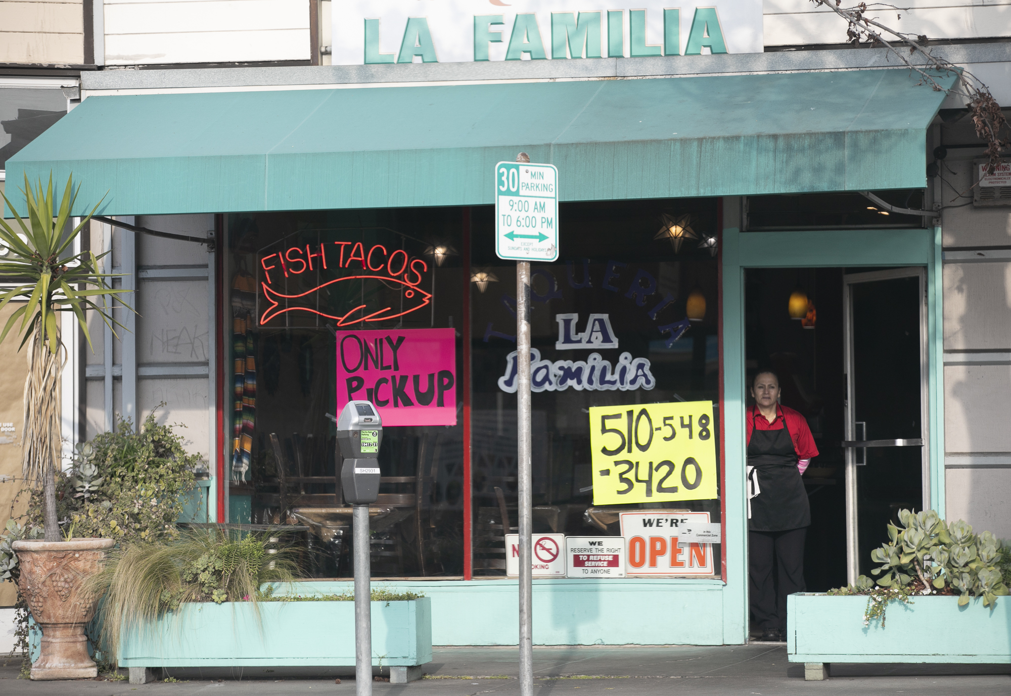 A restaurant employee in the doorway of a taqueria in Berkeley, California. Photo by Anne Wernikoff for CalMatters