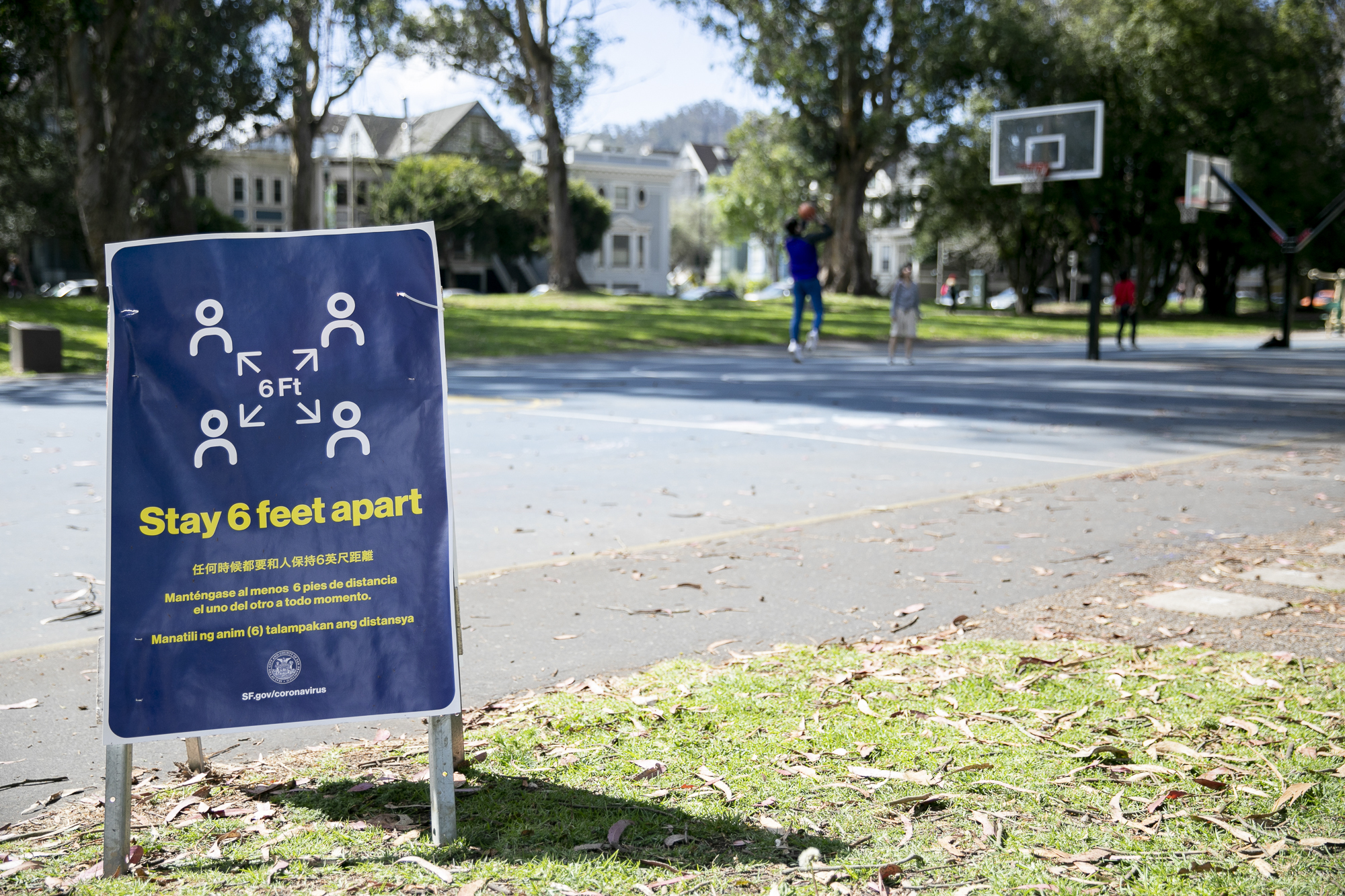 People play basketball at a San Francisco park behind a sign reminders park-goers to maintain social distancing on March 25, 2020. Photo by Anne Wernikoff for CalMatters