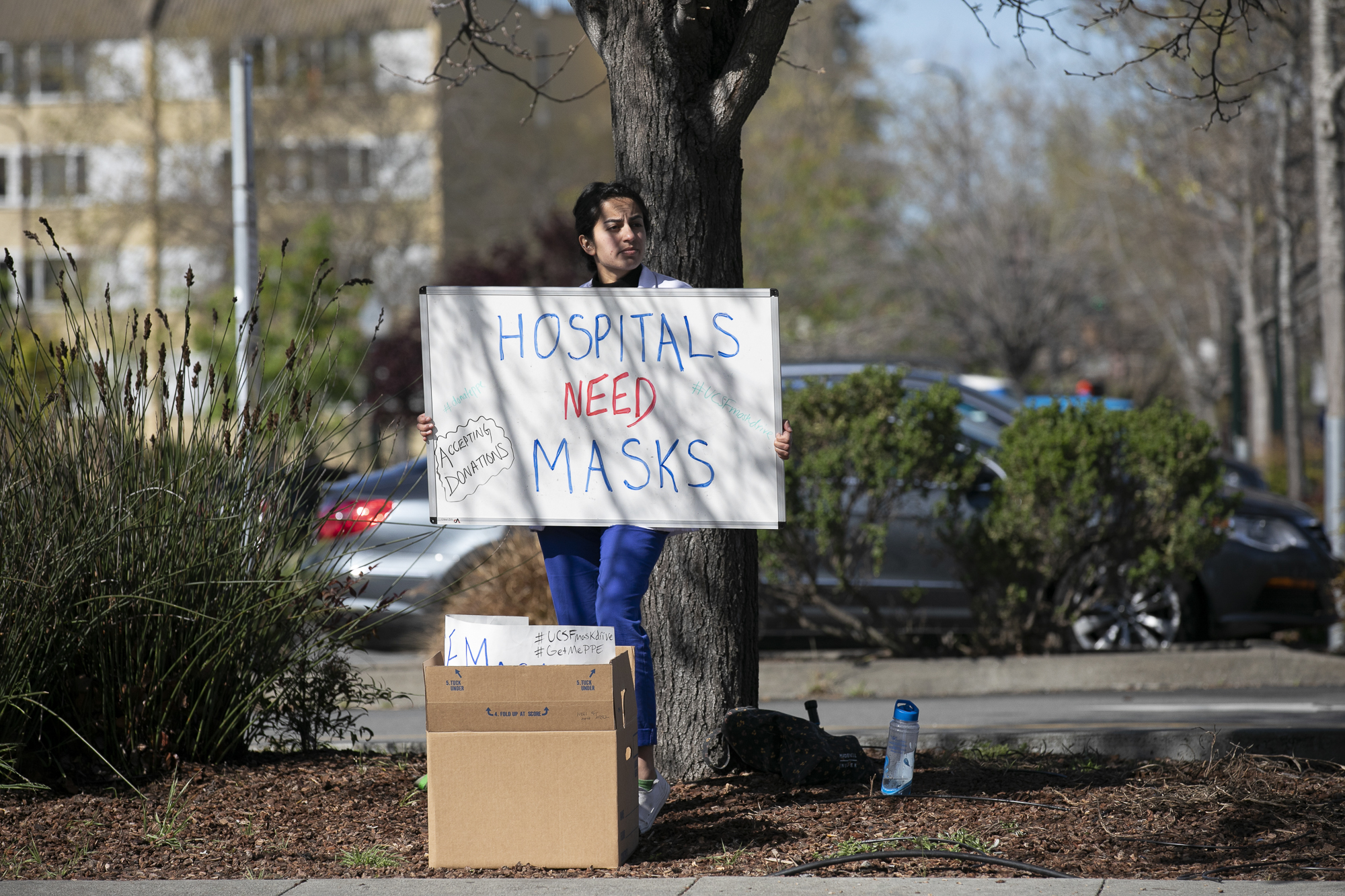 Medical student Shreya Thatai holds up a sign outside of Berkeley Bowl asking for mask donations to help healthcare workers. California Gov. Gavin Newsom promises to have solved the shortage by cutting a massive deal for new masks. Photo by Anne Wernikoff for CalMatters