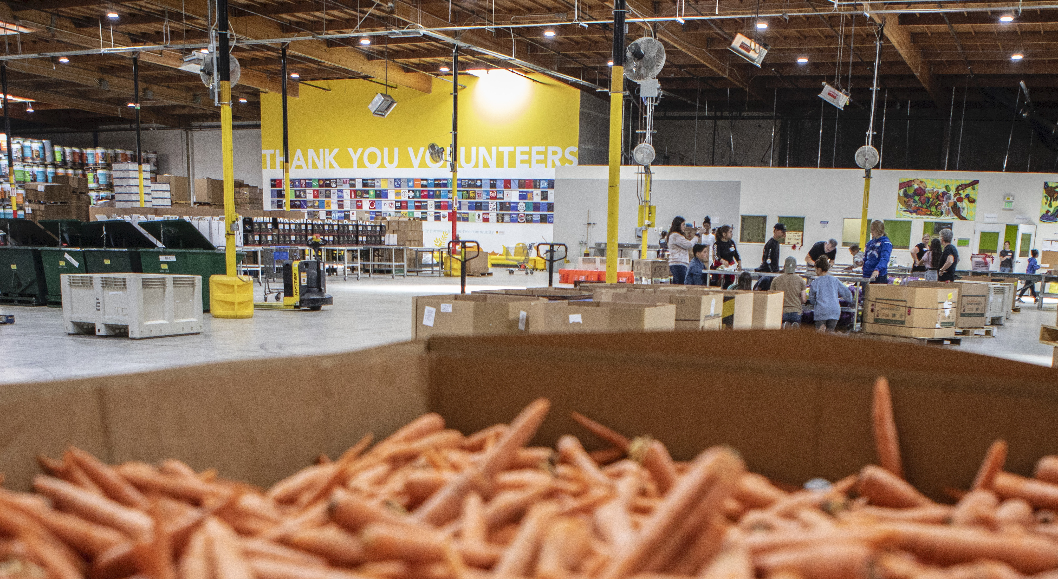 A large sign hangs over the warehouse that says, 'Thank you volunteers' in the volunteer center at the Alameda County Community Food Bank on July 25, 2019. The food bank relies on roughly 100 volunteers every day to package thousands of meals to be distributed. Photo by Anne Wernikoff/CalMatters