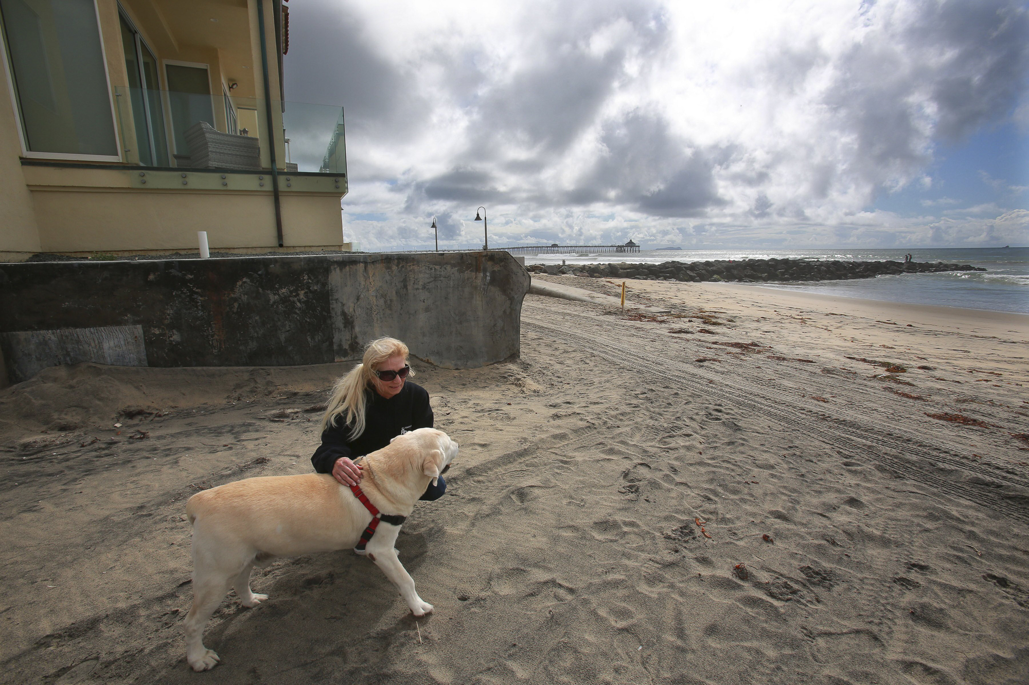 Imperial Beach resident Brenda Clark on the sand with her dog Cooper, March 2020. Photo by Peggy Peattie for CalMatters