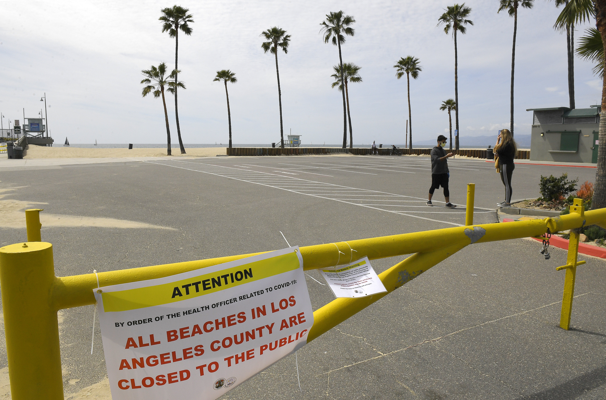 """Pedestrians walk through an empty parking lot at Venice Beach on March 28 — a week after Gov. Gavin Newsom barred 40 million residents from going outdoors except for essentials. Some evidence suggests that may be helping California """"bend the curve"""" of rising coronavirus casualties. Photo by Mark J. Terrill, AP Photo"""