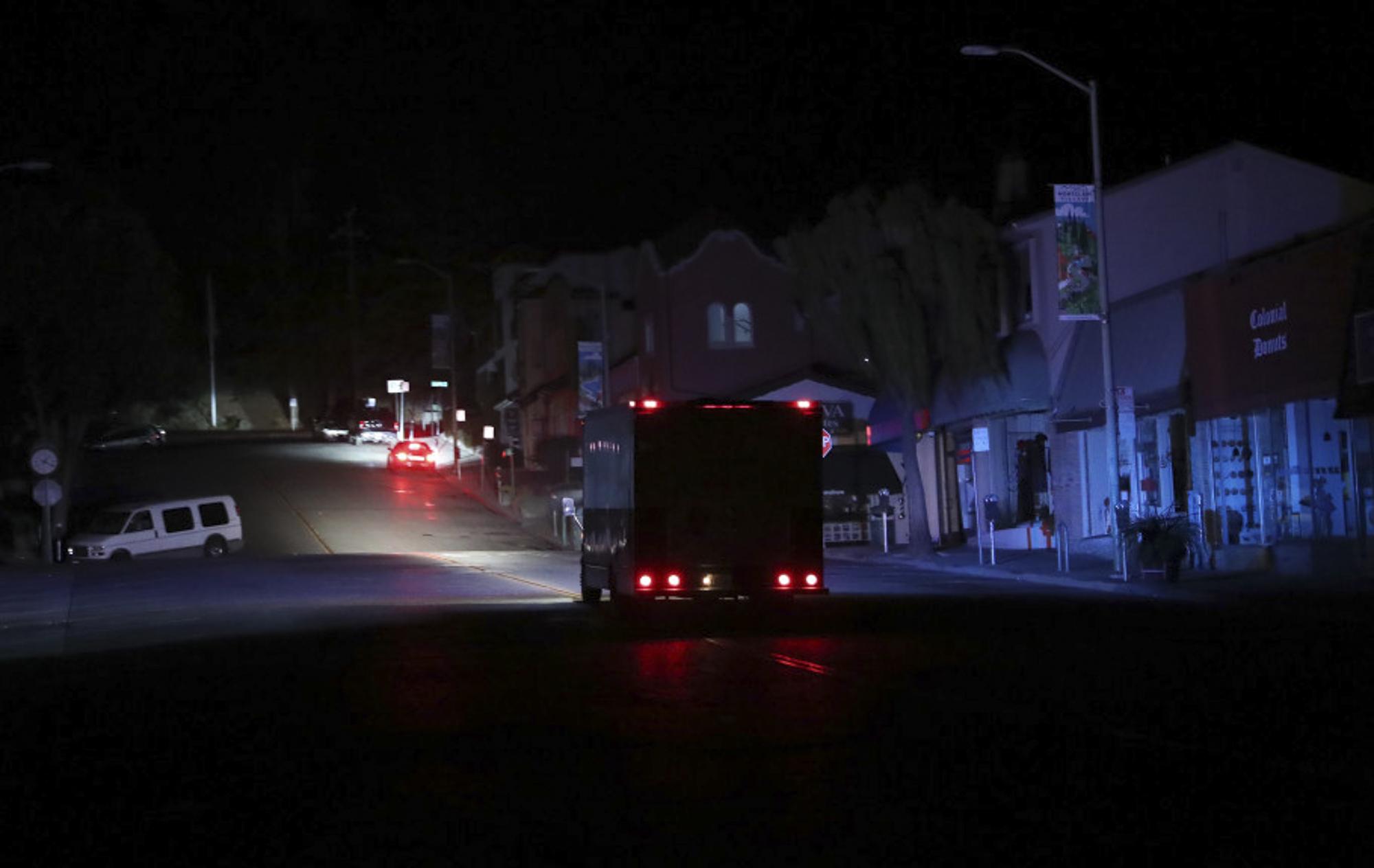 A police vehicle patrols a dark street after PG&E shut off power in Oakland, California, last year. Photo by Jane Tyska, Bay Area News Group