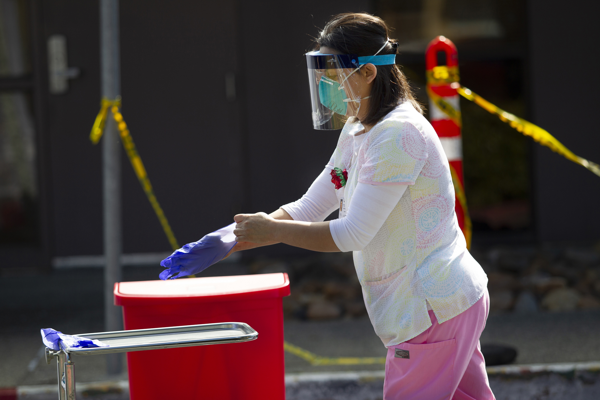 Kaiser Permanente Registered Nurse Rosa Aceves discards her gloves after administering a COVID-19 test at a drive up testing location at the Kaiser Permanente Fremont Medical Center in Fremont on March 11, 2020.