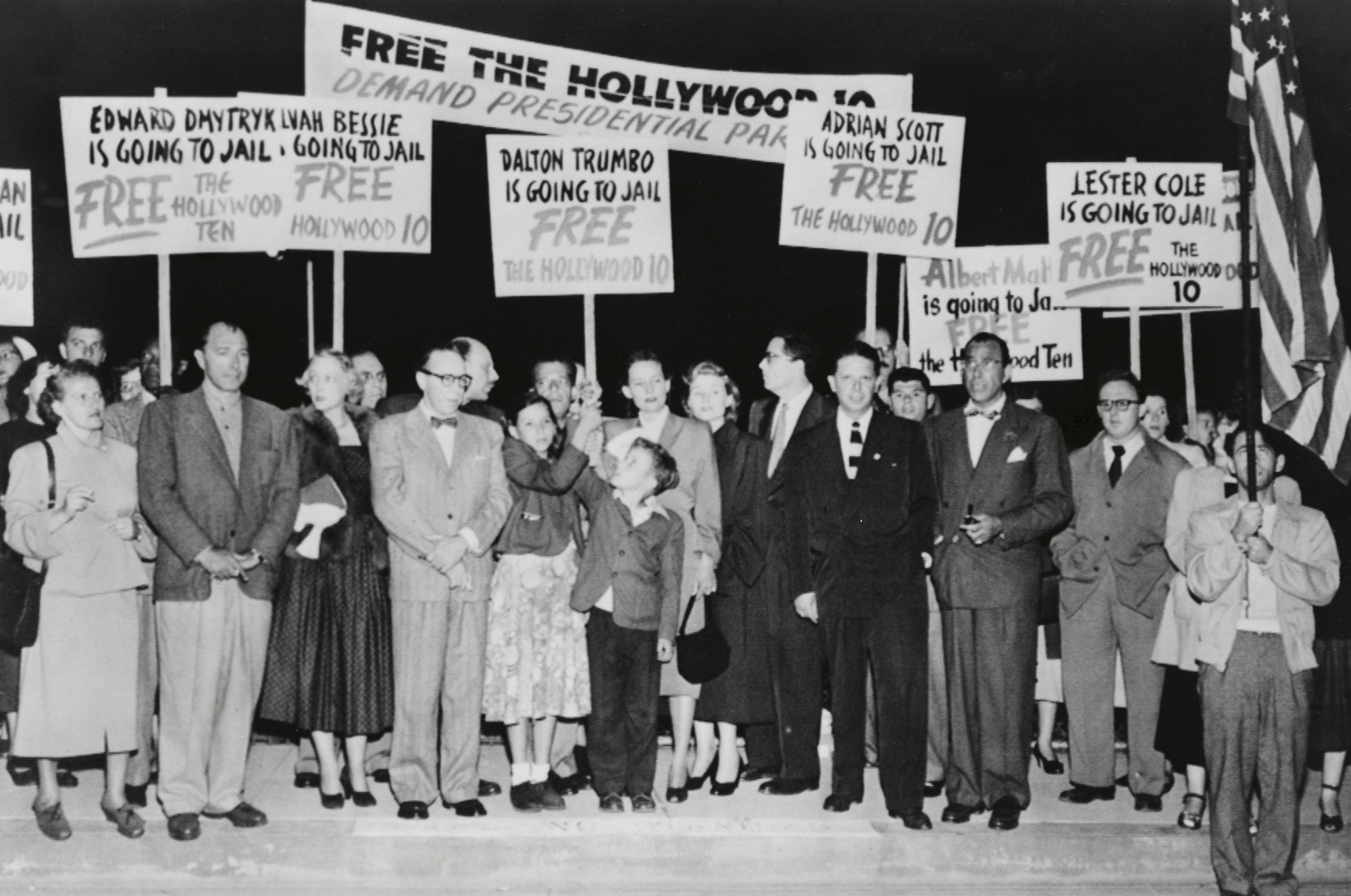 Hollywood ten supporters carrying signs in protest as Dalton Trumbo waits to board a plane on his way to federal prison for refusing to testify to the House Un-American Activities Committee. Photo via Shutterstock