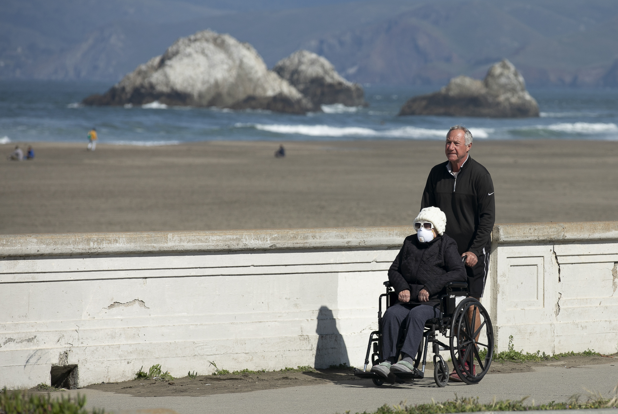 Beach goers enjoy the sunshine in San Francisco on April 7, 2020. Last week, the CDC recommended that everyone wear protective masks while in public to help limit the spread of COVID-19. Photo by Anne Wernikoff for CalMatters