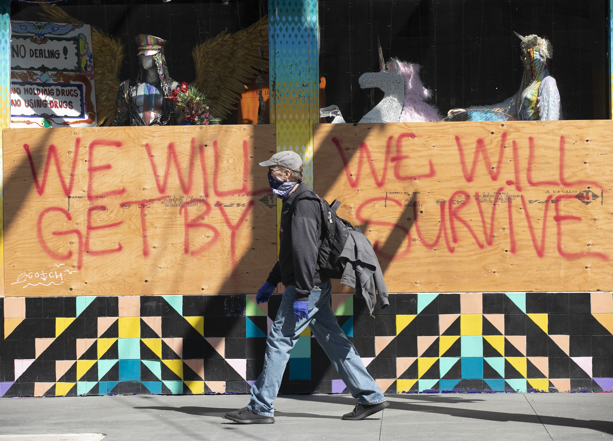 A man wearing disposable gloves and a bandana over his face walks past a boarded up shop on Haight Street in San Francisco on April 7, 2020. California is entering the fourth week of sheltering in place to limit the spread of the novel coronavirus, and the number of Californians hospitalized and those in ICUs with COVID-19 is starting to edge up only slightly. Photo by Anne Wernikoff for CalMatters
