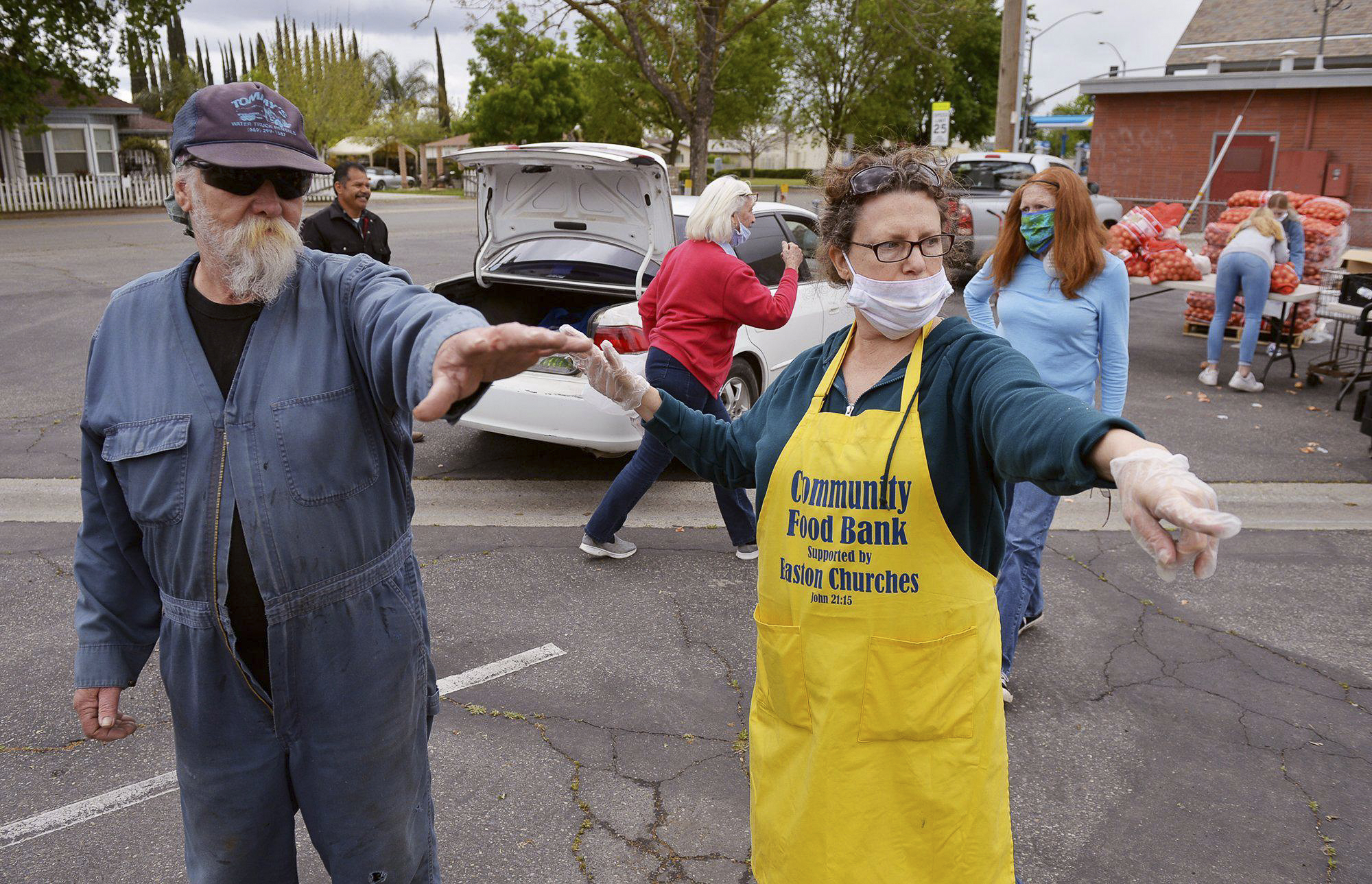 Victoria Salwasser, right, directs Curtis Smith, left, as volunteers distribute food to families in cars at a food bank giveaway held at Easton Presbyterian Church Monday, April 6, 2020 in Easton. Photo by Eric Paul Zamora, The Fresno Bee