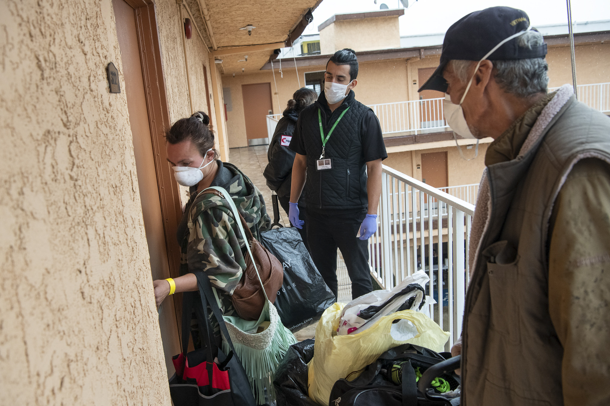 Cassie Gamboa, left, and Robert Romo, right, go into their new hotel room with Edwin Aviles, of Union Station Homeless Services on Tuesday, April 7, 2020. Photoby Michael Owen Baker courtesy of Los Angeles County