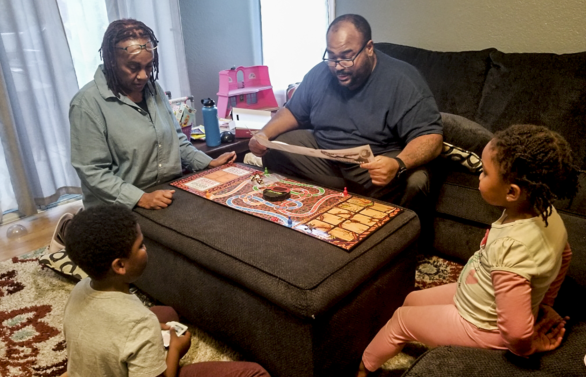 Joshua Martin and his two children, 4-year-old Olivia and 9-year-old Matthew, play Jumanji with their grandmother Shelley McCall. McCall has been babysitting the children since schools closed because Martin and his wife are both healthcare workers but they worry about her health. Photo courtesy the Martin Family