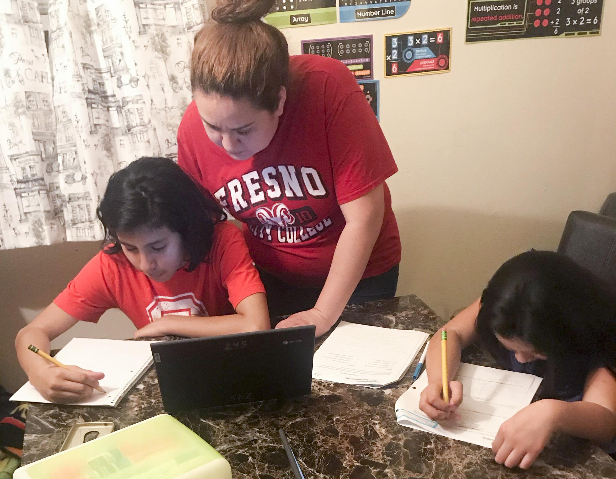 Amanda Reyes helps her kids Claudio, 13, and Evangelyn, 9, with their school work. Photo courtesy of Amanda Reyes