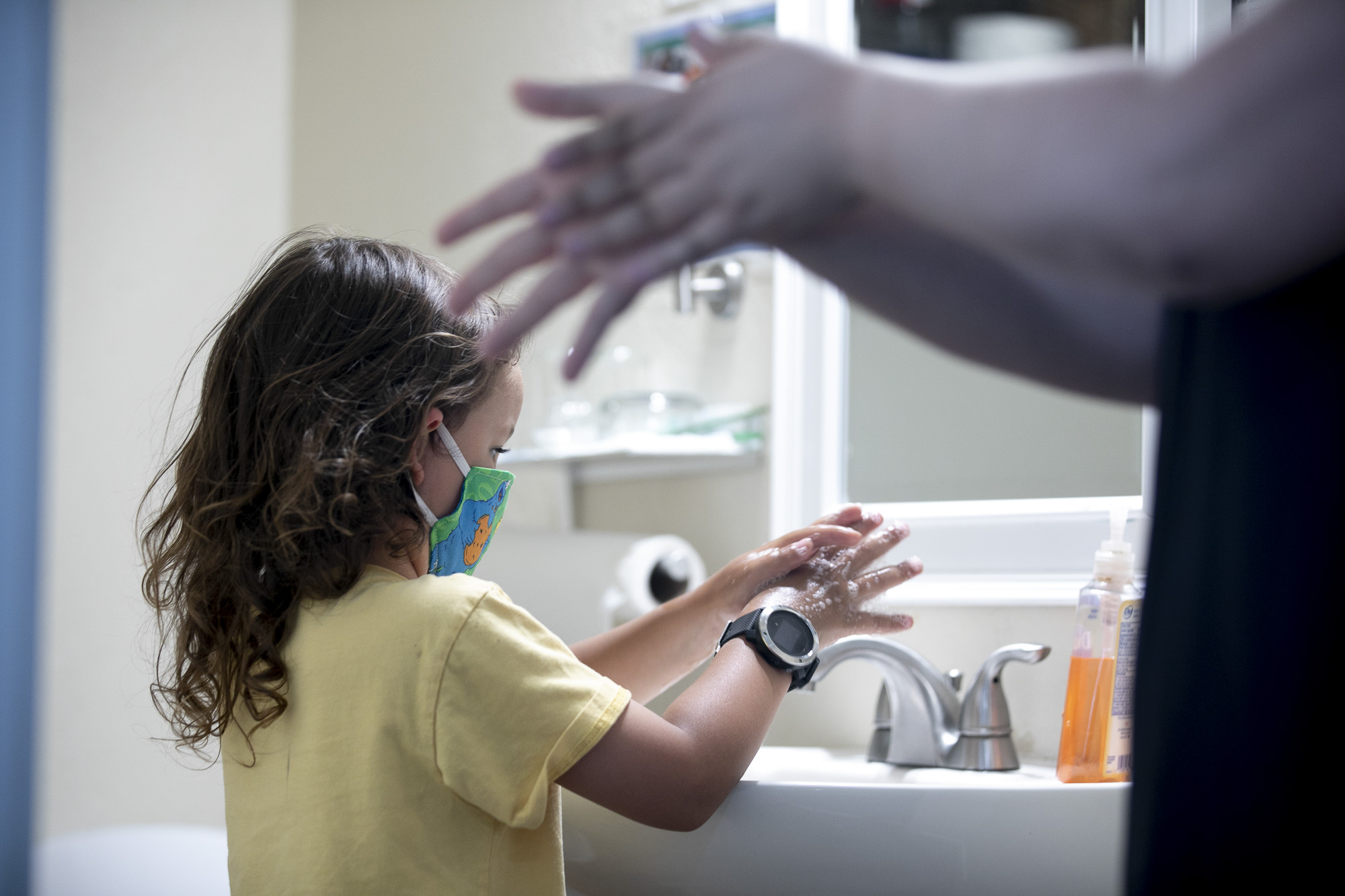 Noah, 5, washes his hands as a Heritage employee Becky Garcia acts out the motions for him to follow. Students and teachers only wear masks while doing indoor activities unless a student's parent has requested they wear them all the time. Photo by Anne Wernikoff for CalMatters