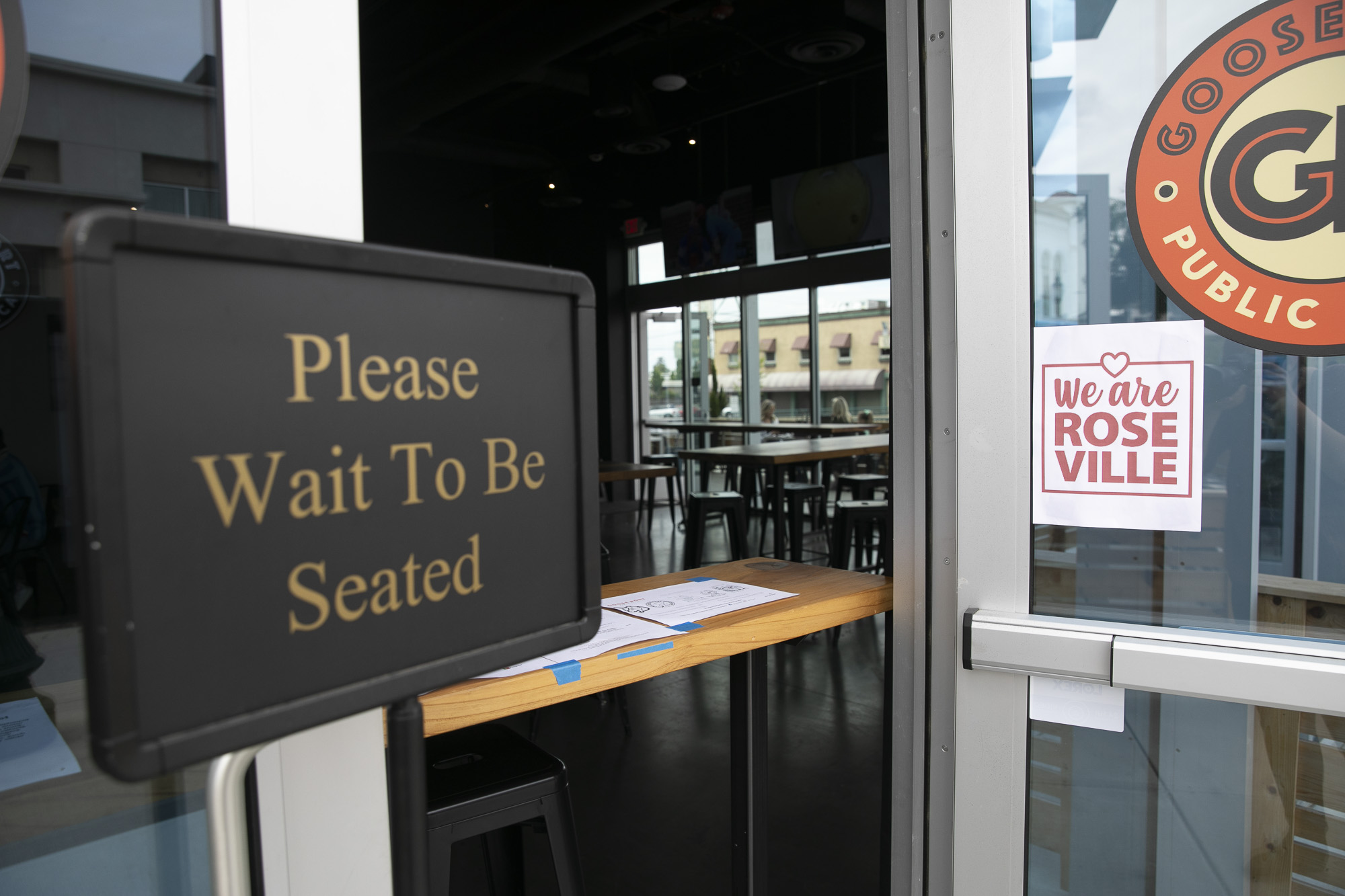 A table blocks patrons from entering the dining room at Roseville pub Goose Port on May 14, 2020. The restaurant and bar has opened their patio for dine-in service and plans to fully re-open for indoor dining tomorrow. Photo by Anne Wernikoff for CalMatters