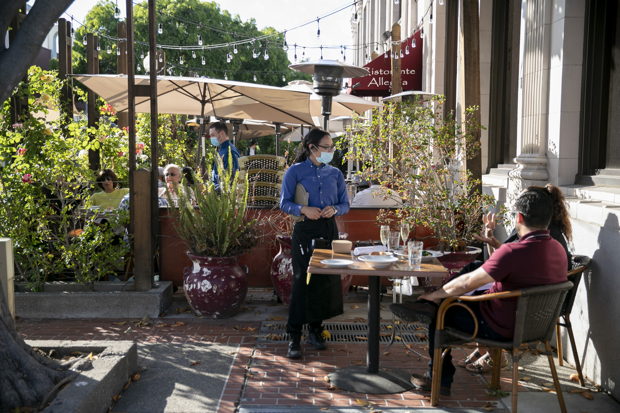 A masked server speaks with guests at Ristorante Allegria in Downtown Napa on May 22, 2020. The bustling restaurant has been busy since reopening their dining room and patio earlier this week. Photo by Anne Wernikoff for CalMatters