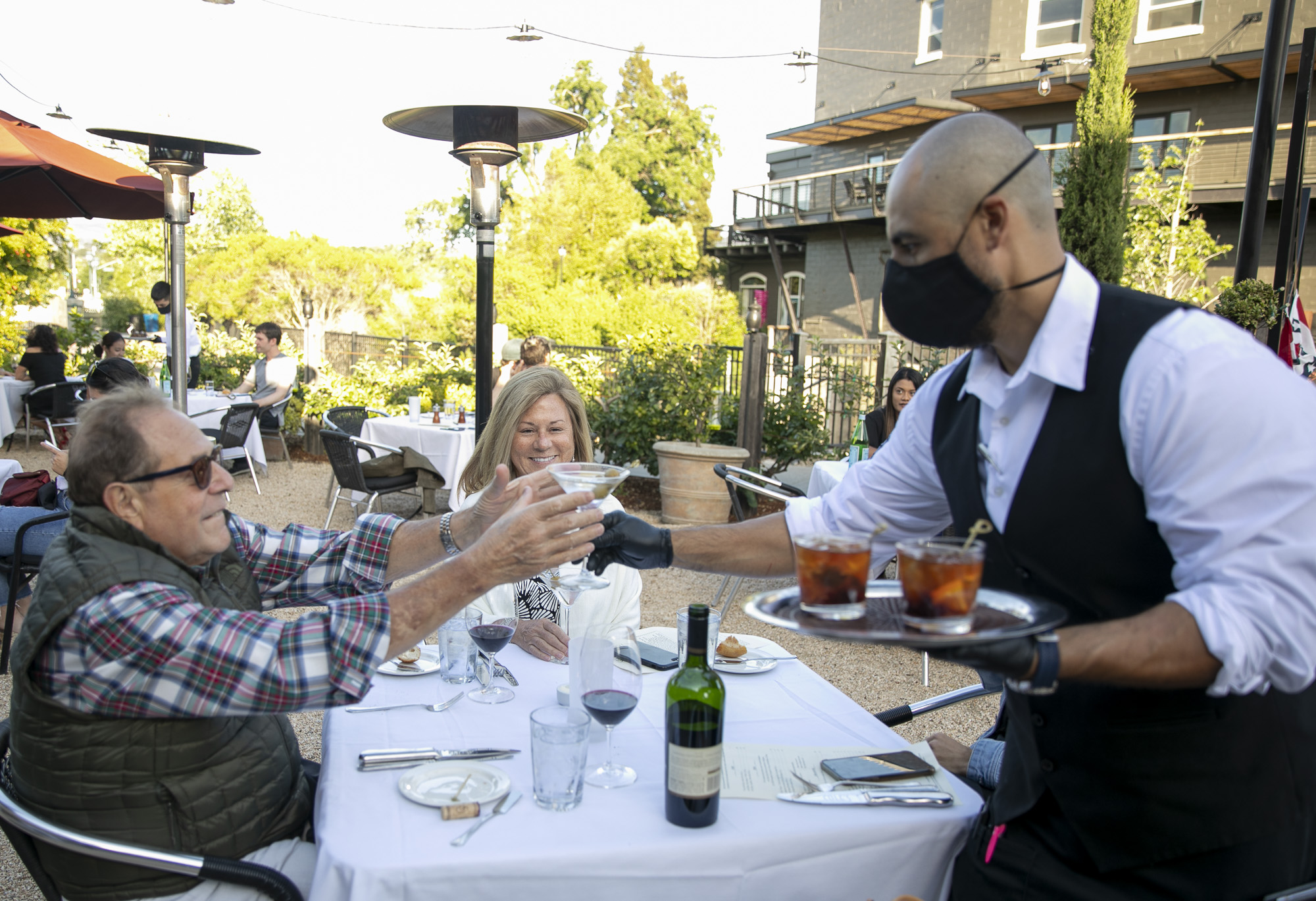 Doug Mahon reaches for a cocktail from a masked server at Cole's Chop House in Downtown Napa on March 22, 2020. The popular steakhouse reopened immediately following the announcement that Napa restaurants could begin dine-in service. Photo by Anne Wernikoff for CalMatters