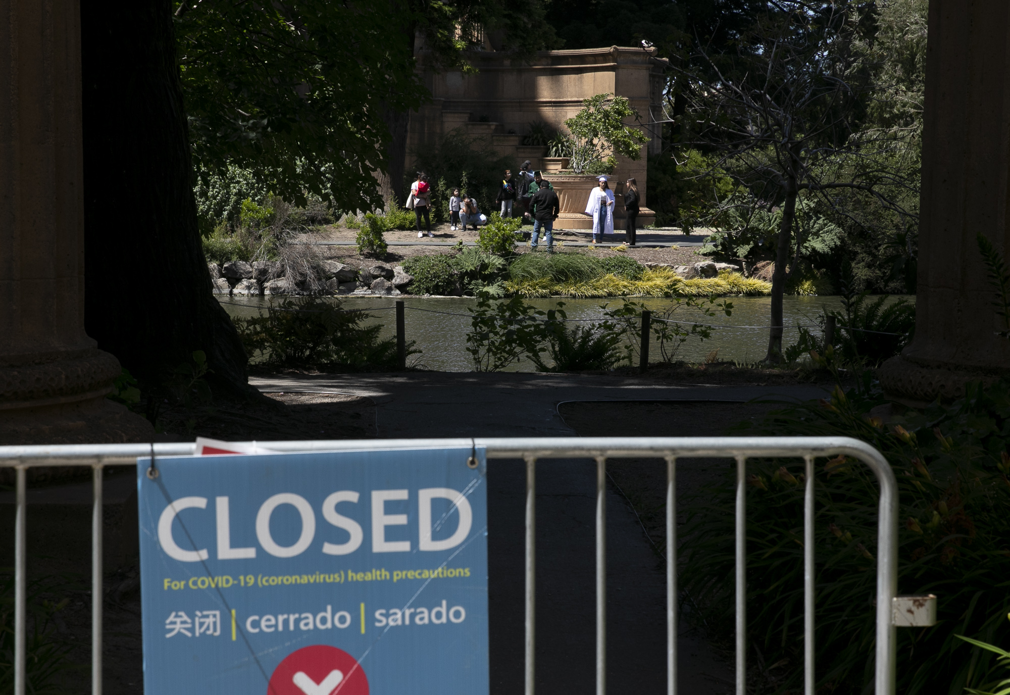 A group takes graduation photos at Palace of Fine arts despite parts of the park remaining closed to the public due to coronavirus concerns over Memorial Day Weekend in San Francisco, May 23, 2020. Photo by Anne Wernikoff for CalMatters