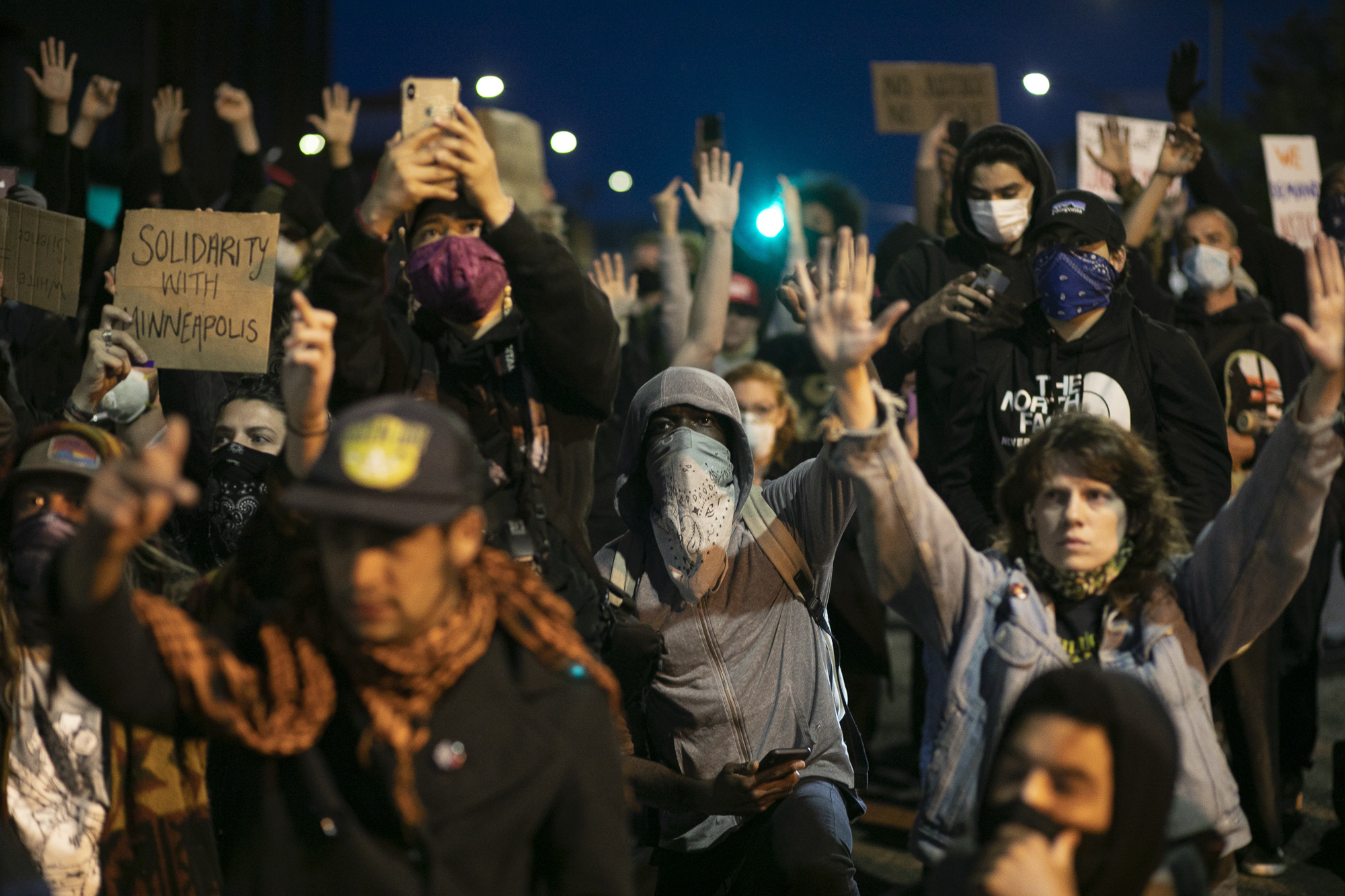 A crowd kneels with their hands up facing a police line during a demonstration Downtown Oakland on May 29, 2020. Thousands took to the streets Friday night in solidarity with protesters in Minneapolis against the killing of George Floyd by Minneapolis police earlier this week. Photo by Anne Wernikoff for CalMatters