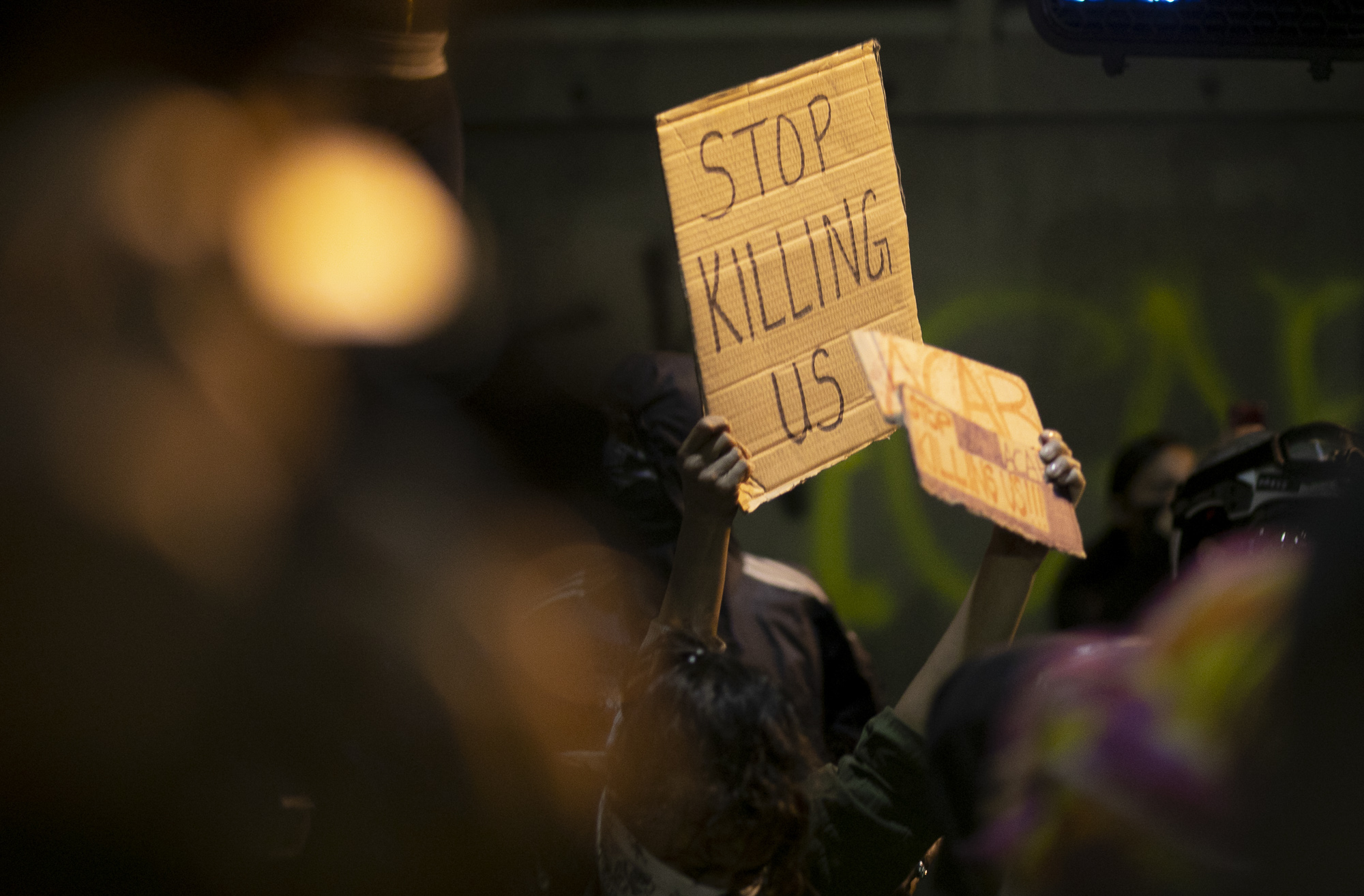 A protester holds up a sign that says 'stop killing us' during a demonstration May 29, 2020 Downtown Oakland. Thousands took to the streets Friday night in solidarity with protesters in Minneapolis against the killing of George Floyd by Minneapolis police earlier this week. Photo by Anne Wernikoff for CalMatters